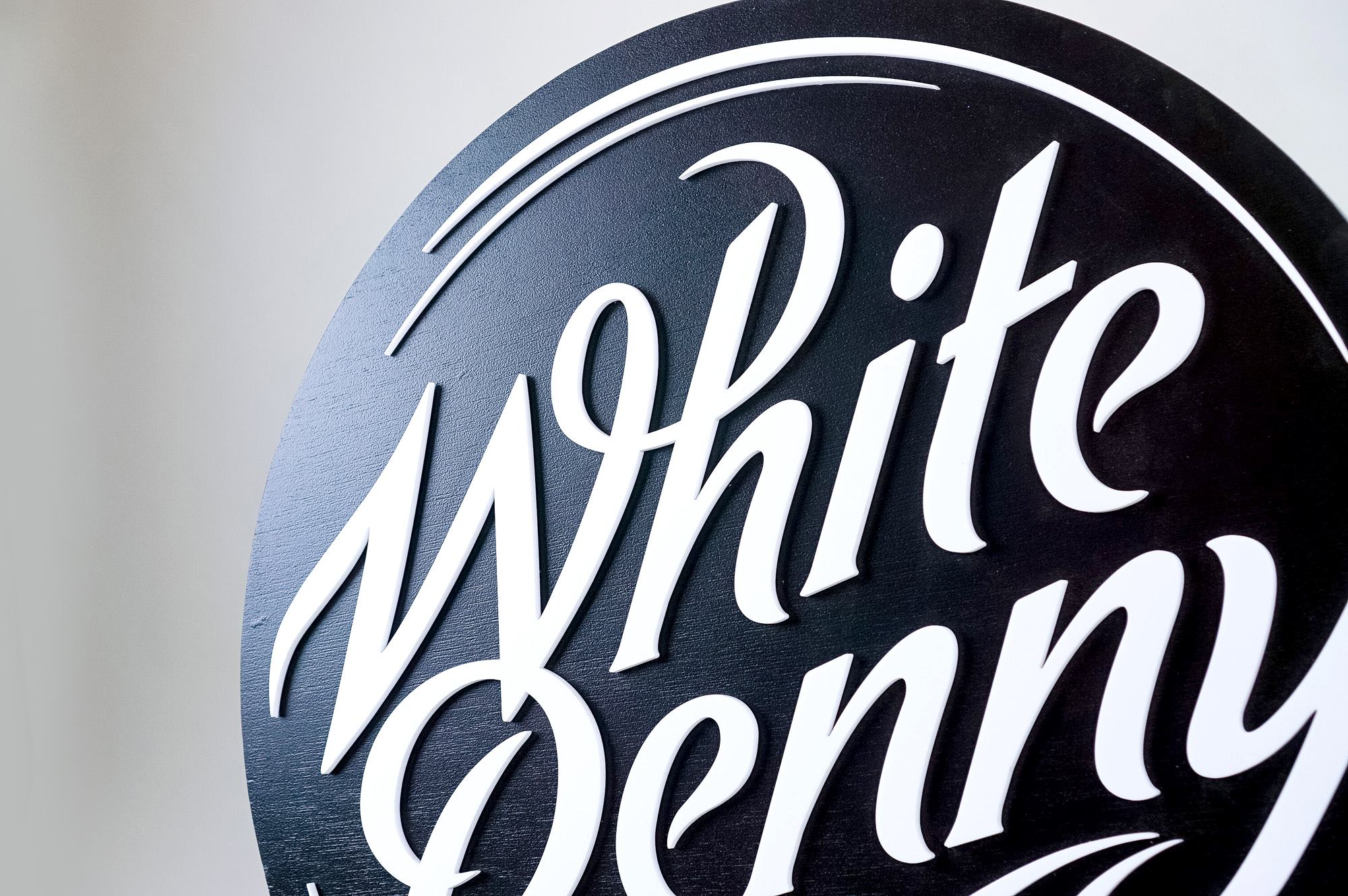 Black and white round raised sign with intricate lettering for Whitepenny, a web development, design and branding firm based in New Jersey.