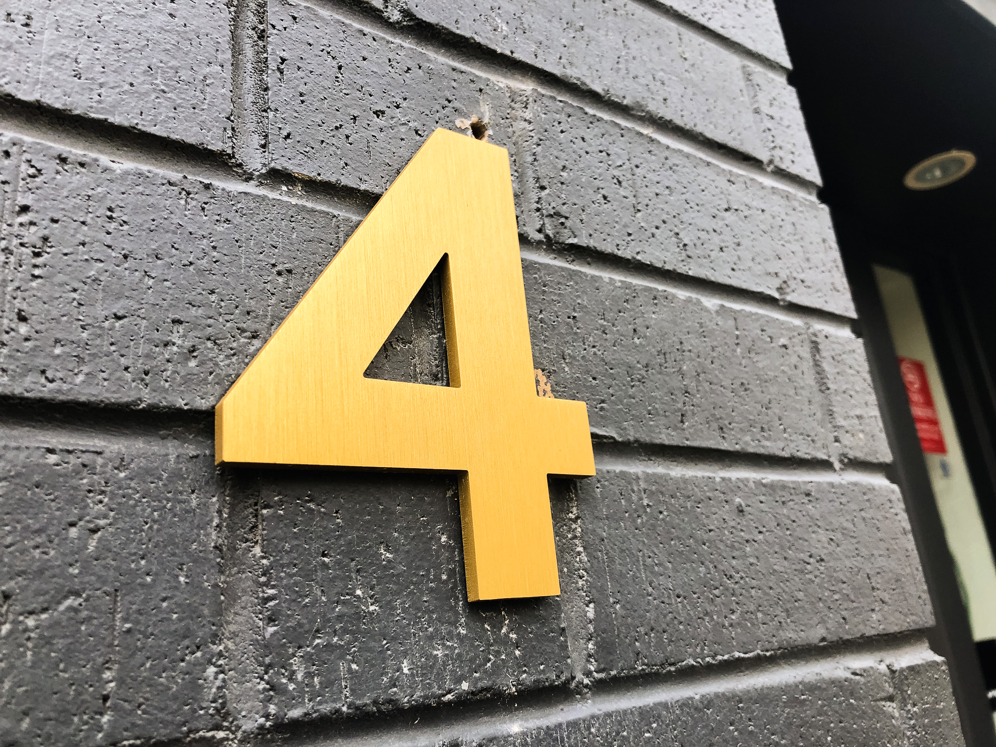anodized brushed gold number on black brick building
