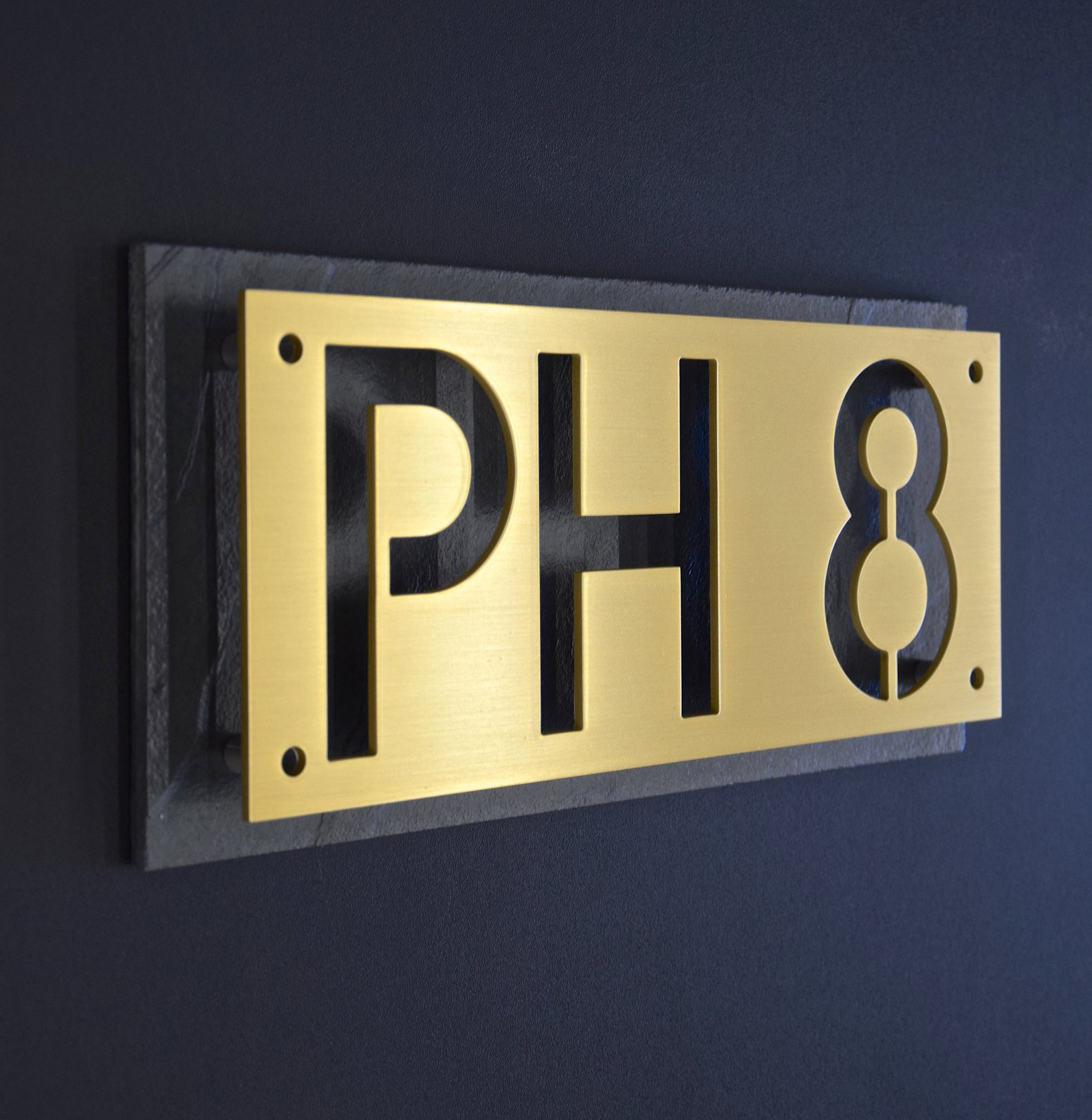 Cutout brass stencil house numbers on black plaque