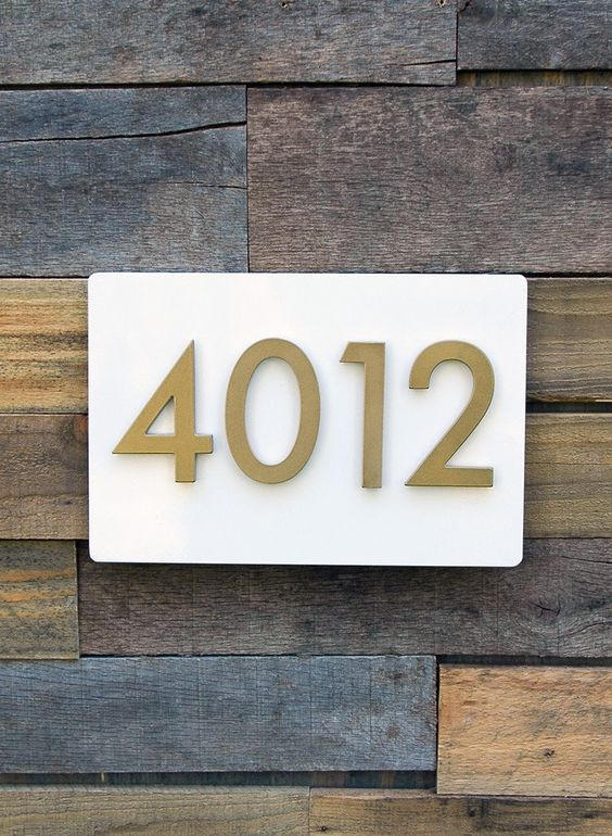 brass house numbers on white panel on reclaimed wood