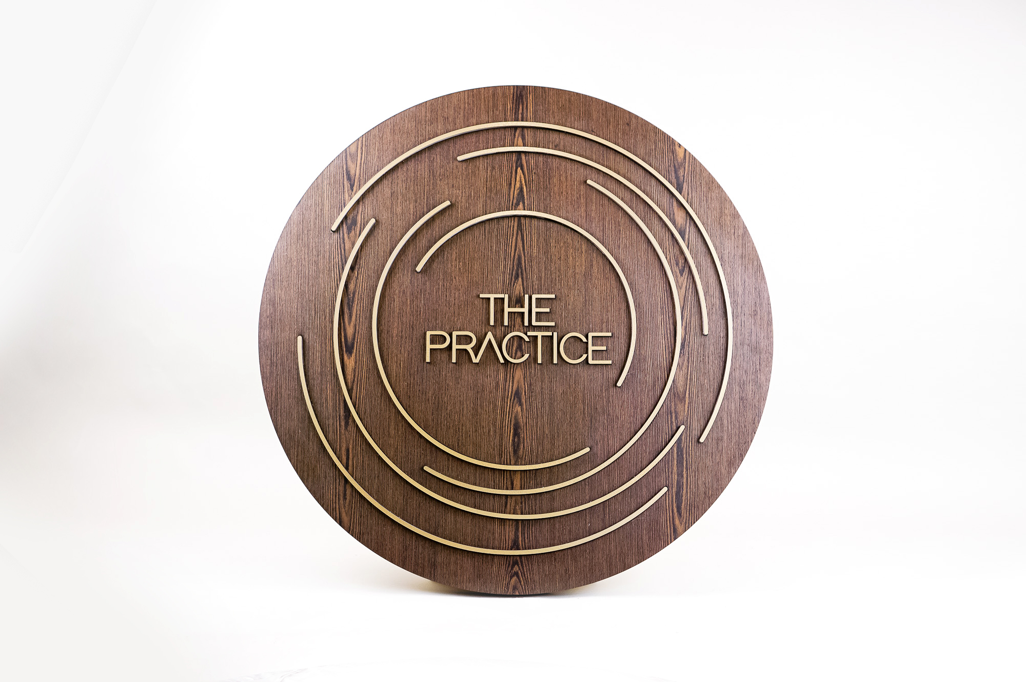 Illuminated dark wood and brass sign for The Practice, a yoga studio at Newtown Athletic Club, a premiere family fitness and wellness center serving residents of Newtown, PA