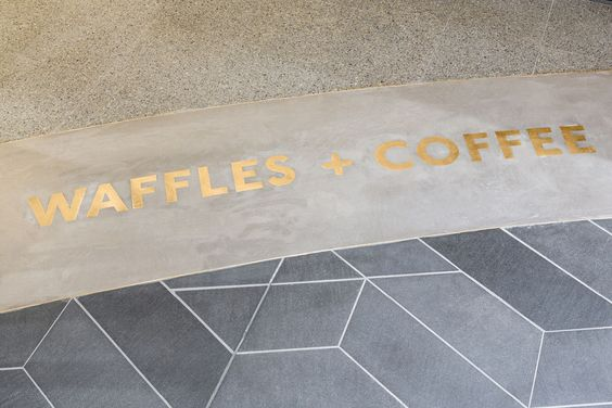 brass letters inlaid on a concrete floor