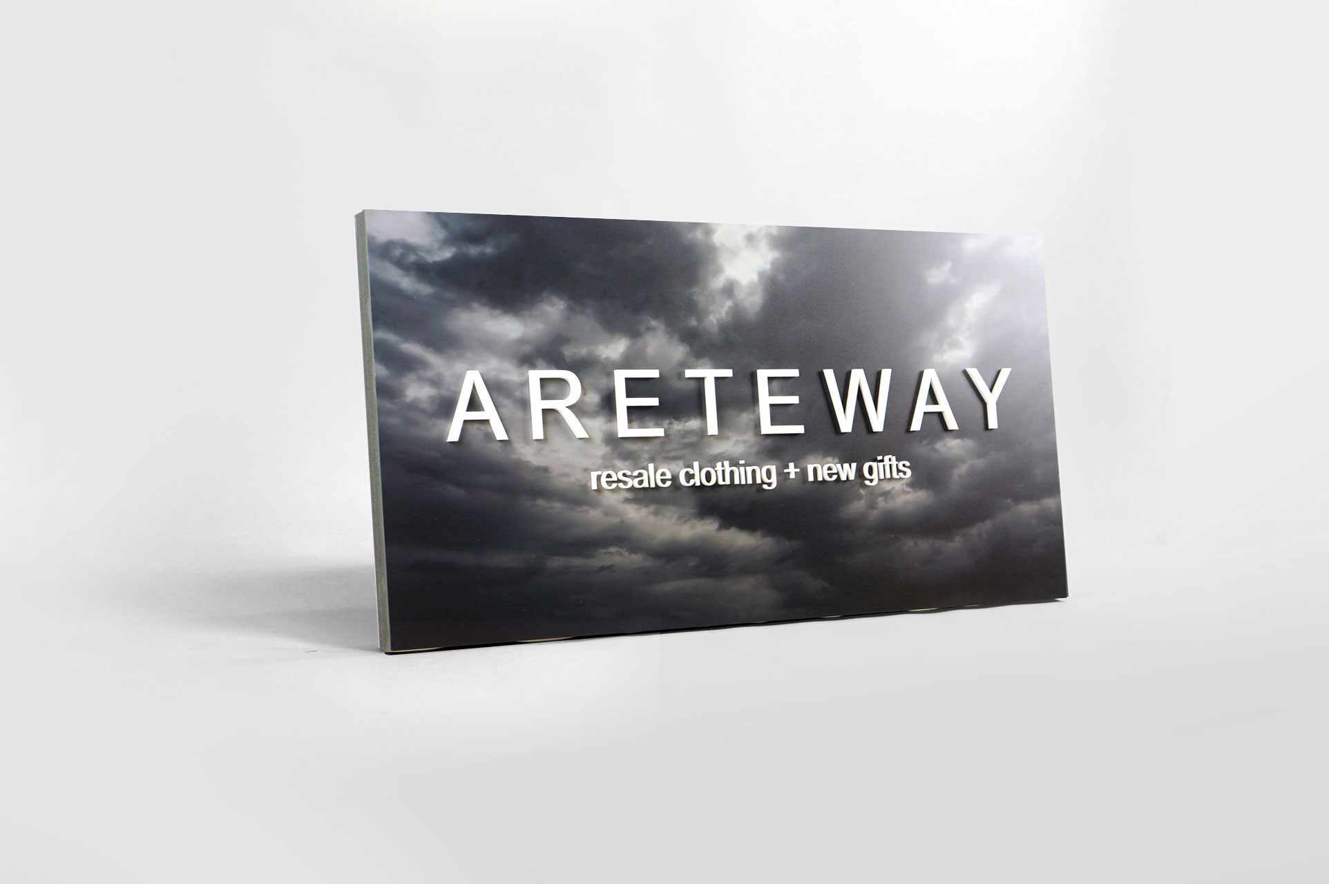 Exterior sign with black and white photo and raised white letters for Areteway, a clothing and gift boutique in Santa Rosa, CA.