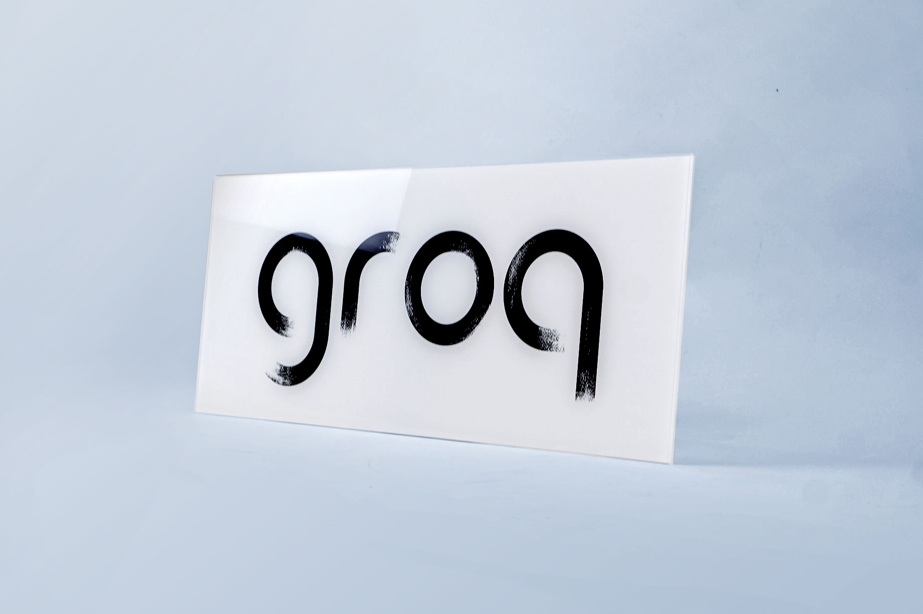 Glassy black and white sign with black brushstroke logo for Groq, a Palo Alto based company developing an integrated circuit developed specifically for machine learning.