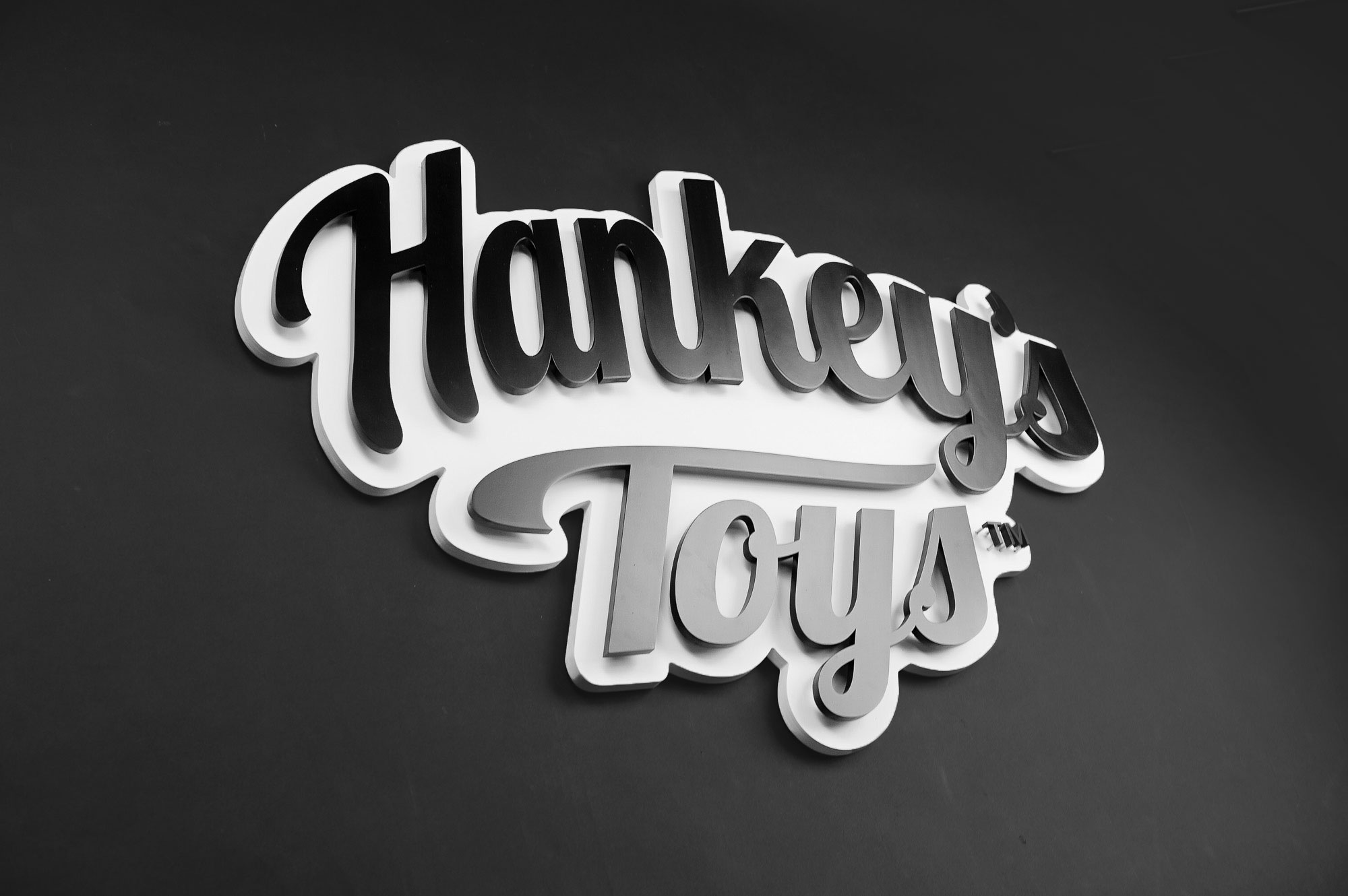 Black and white raised cutout script logo for Mr. Hankey's Toys, maker of handmade adult sex toys.