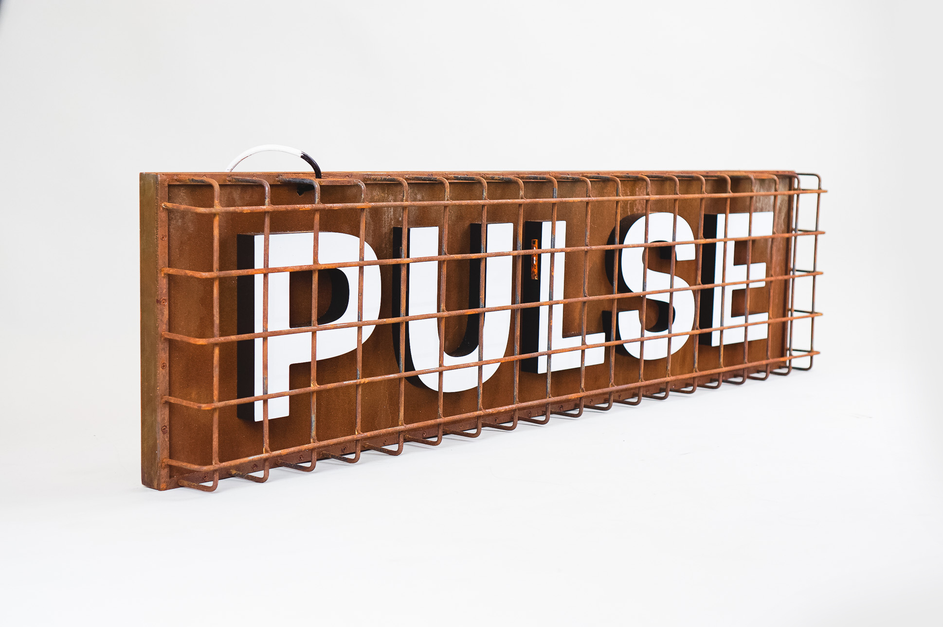 Industrial, caged, rusty metal illuminated sign for Pulse, a fitness studio at Newtown Athletic Club, a premiere family fitness and wellness center serving residents of Newtown, PA