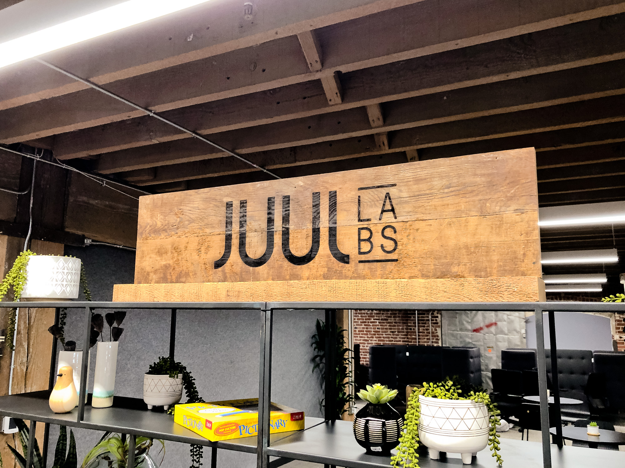 Reclaimed wood sign with etched logo on a shelf for the San Francisco office of Juul, an electronic cigarette company.