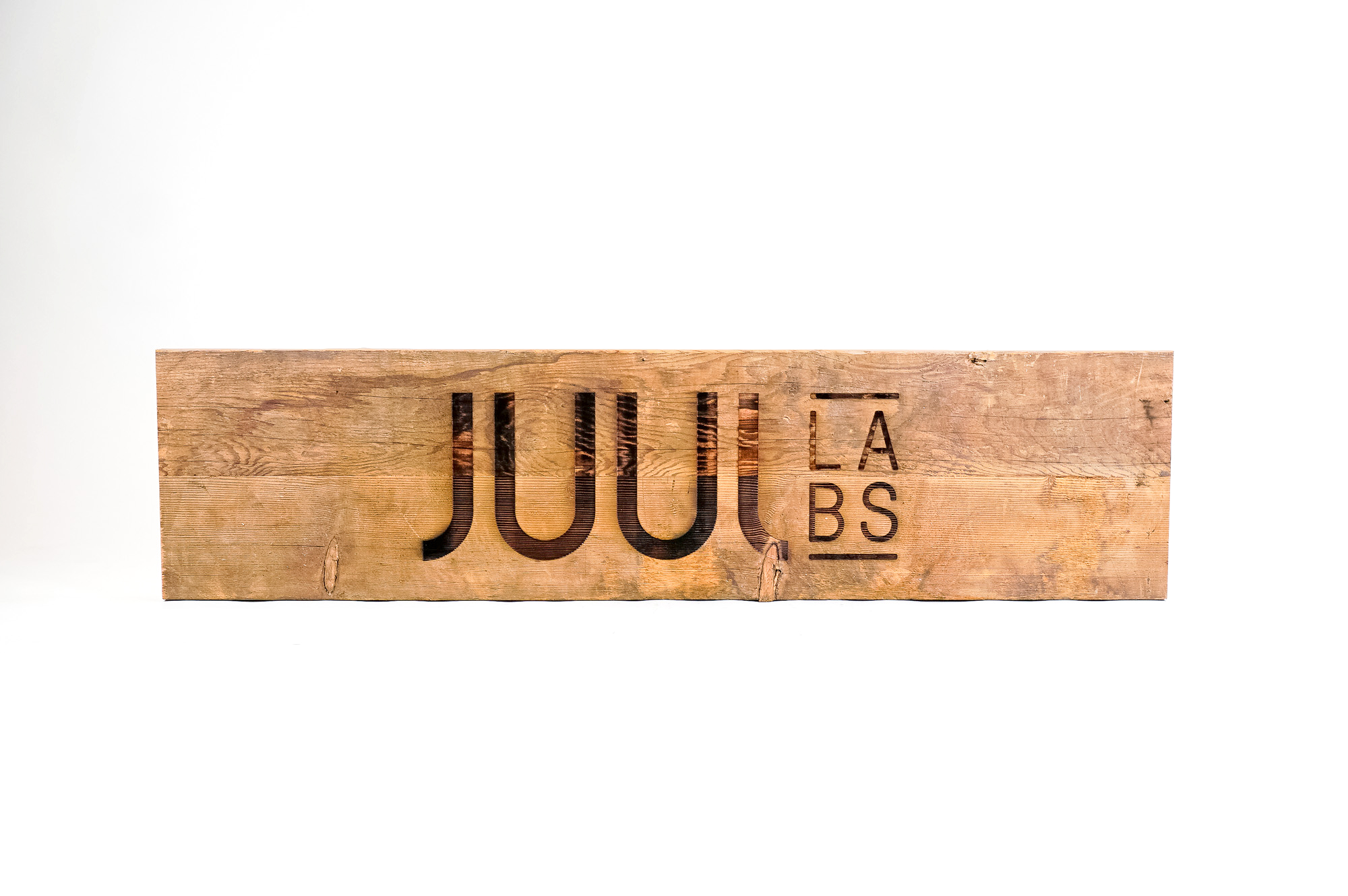 Reclaimed wood sign with etched logo for the San Francisco office of Juul, an electronic cigarette company.
