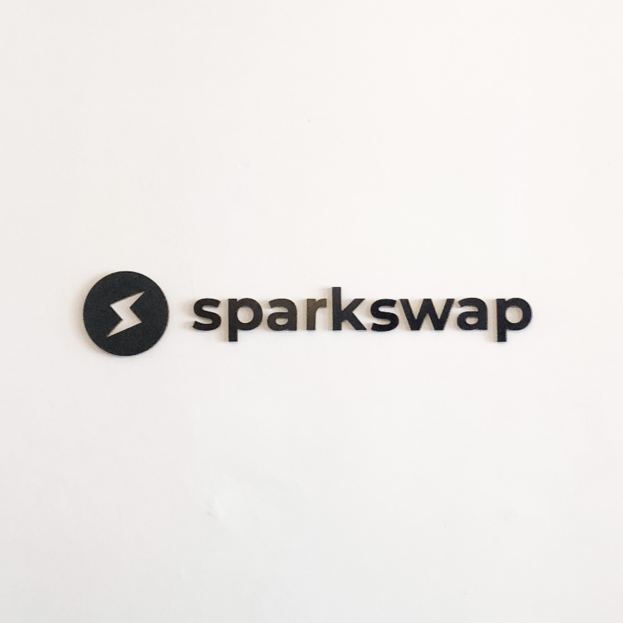 Black painted acrylic logo on white wall for Sparkswap, the first cryptocurrency exchange built on the Lightning Network