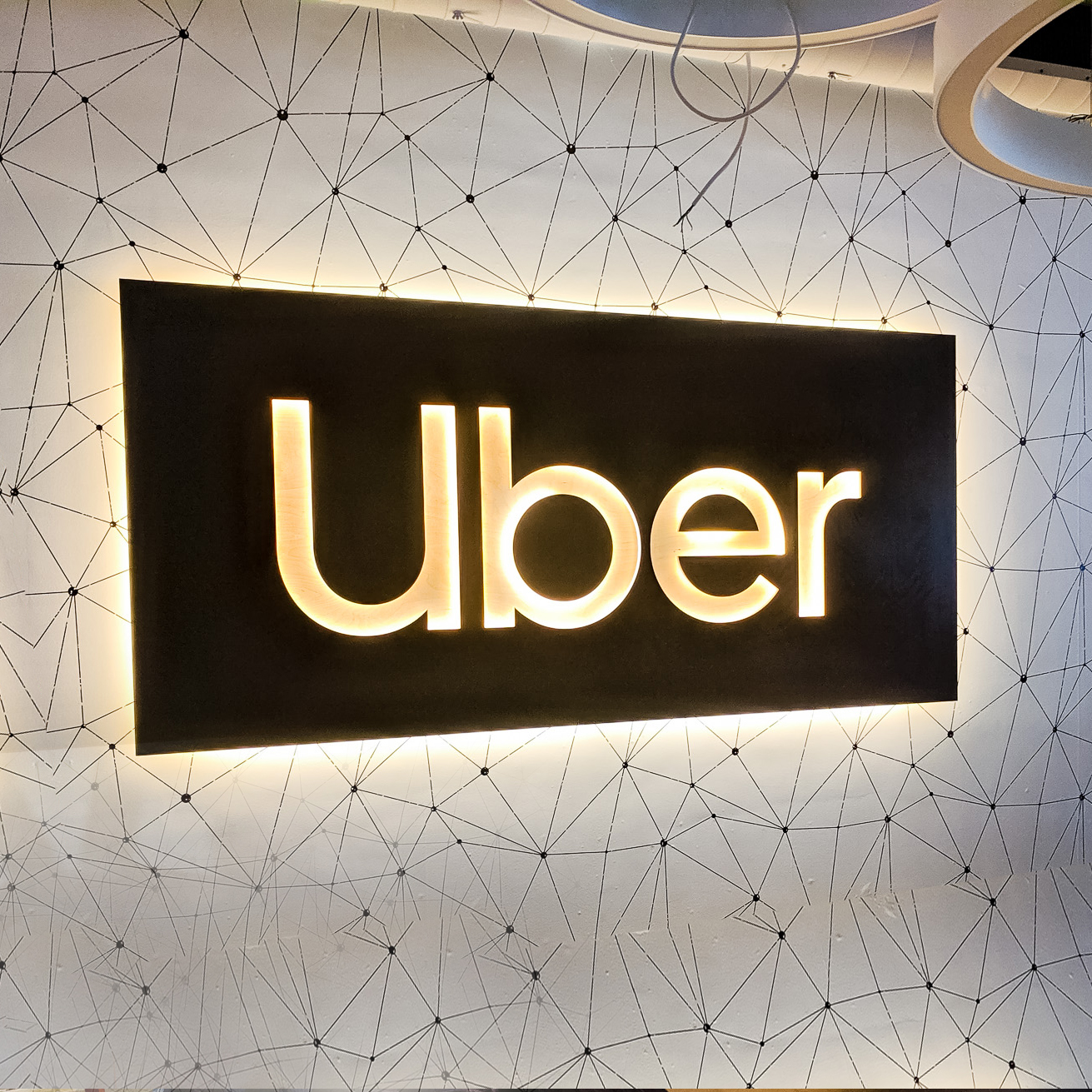 Illuminated black wood lobby sign with warm light on geometrical wallpaper for Uber, an American multinational transportation network company..