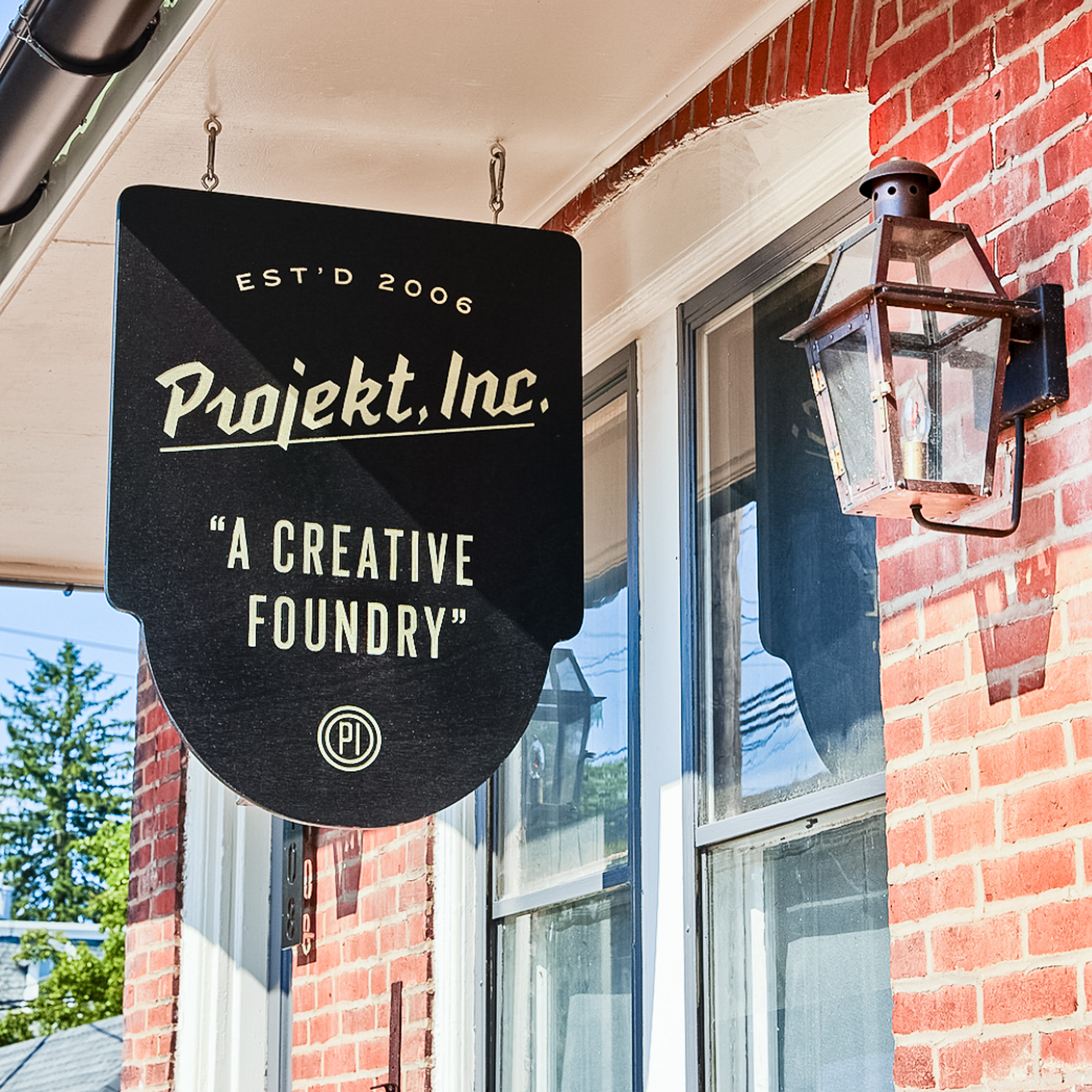 Suspended nodern black entrance sign for Projekt, a creative foundry in North Wales, PA