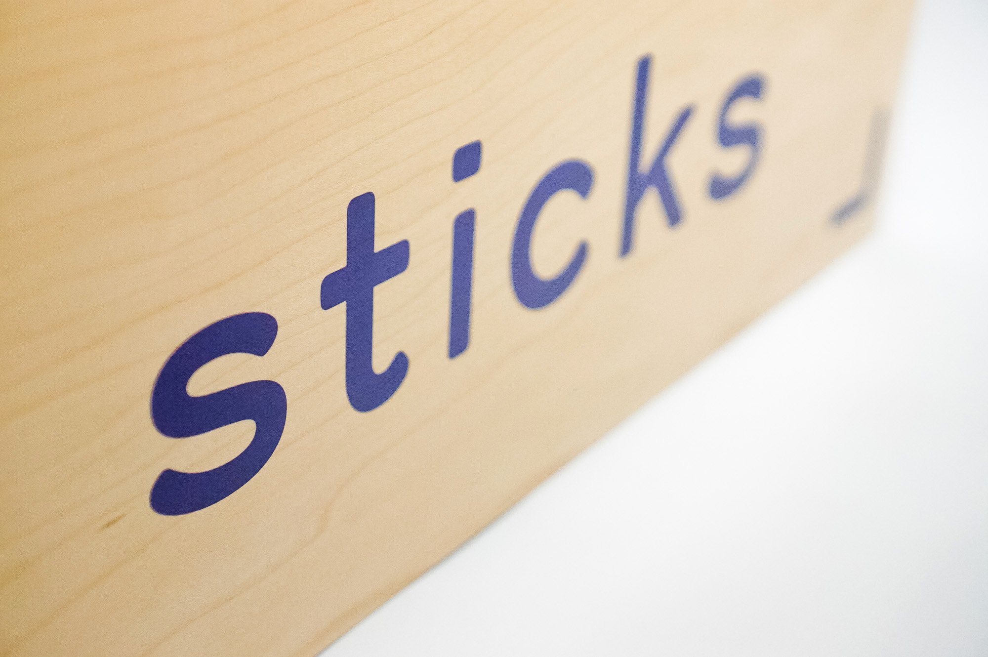 Light wood event sign with blue logo for Sticks, a kidswear company.