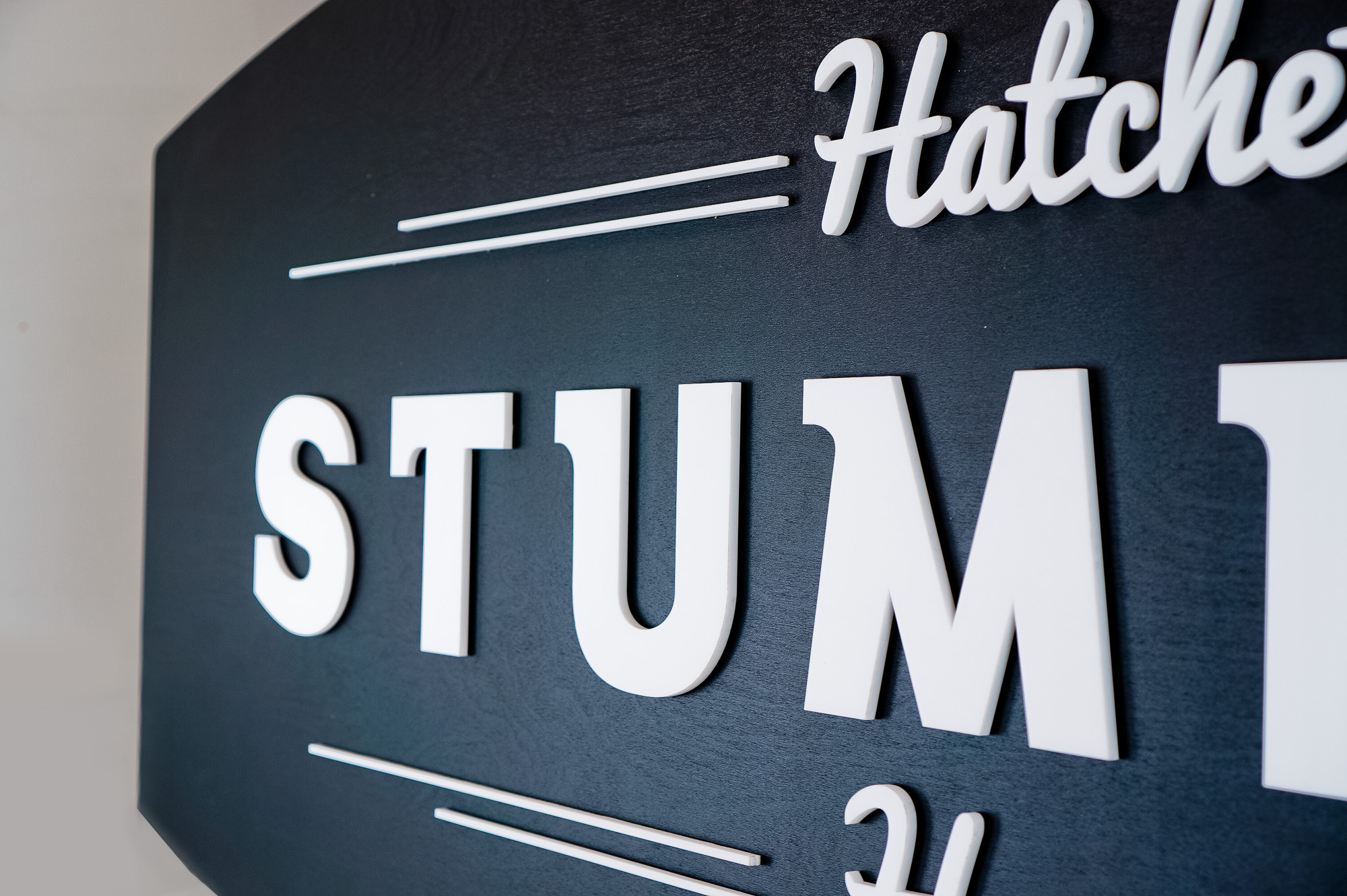 Black and white raised panel sign for Stumpy's, the first hatchet throwing venue in the U.S.
