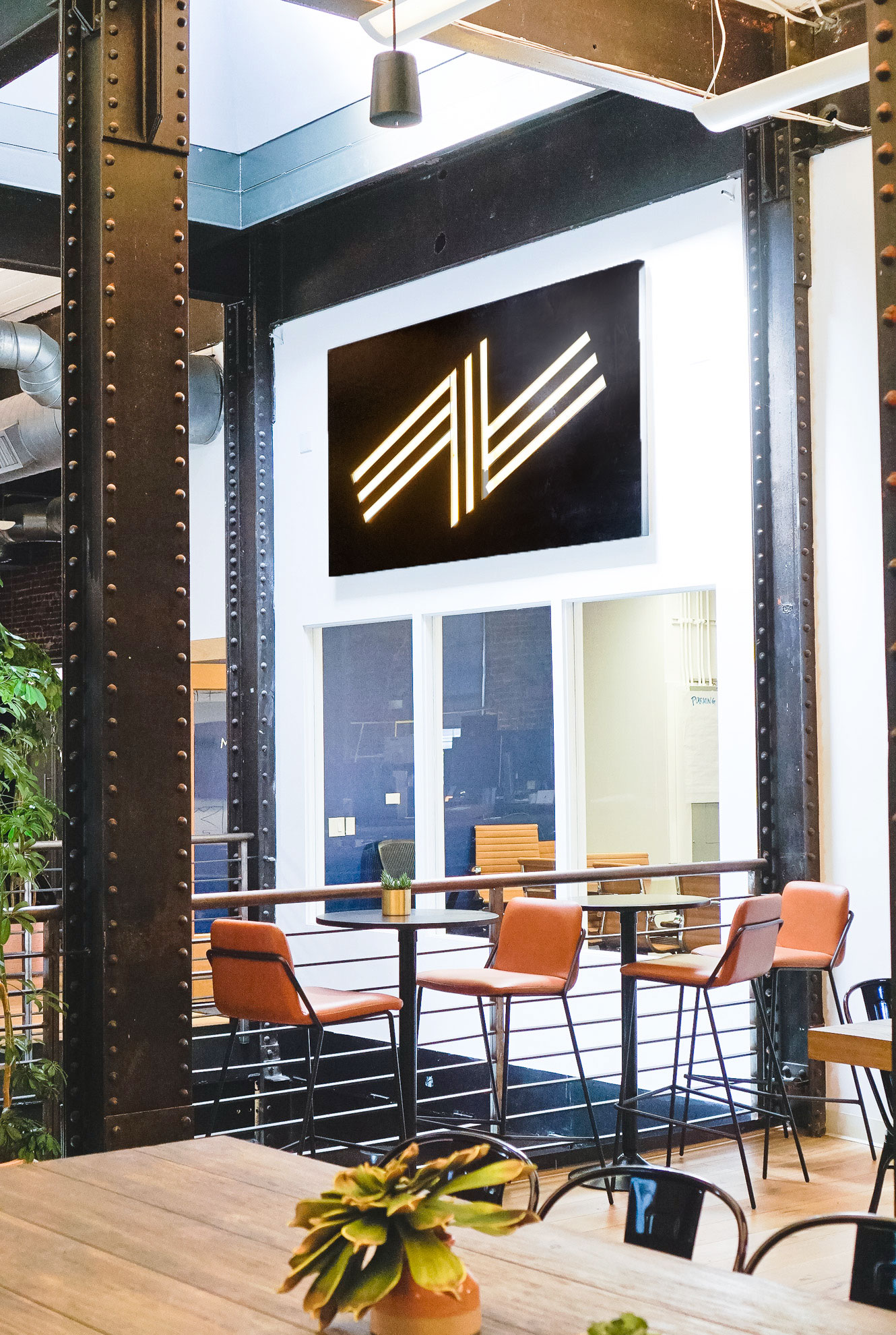 Illuminated black wood sign with warm light on the atrium wall of Zeus, a San Francisco based company providing beautiful, fully furnished homes for business travelers staying one month or longer.