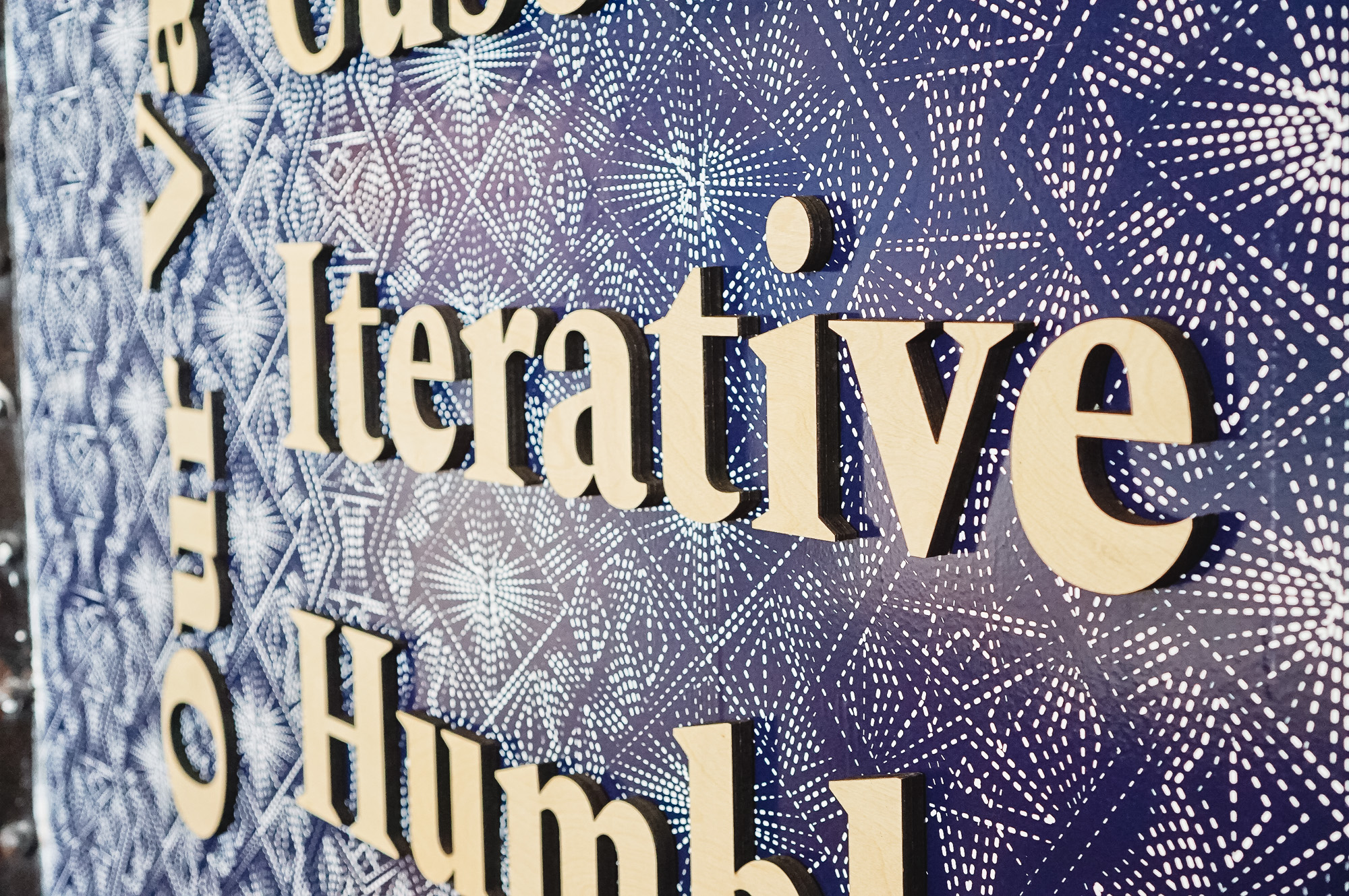 Light wood letters on blue geometric patterned wallpaper for the lobby of Zeus, a San Francisco based company providing beautiful, fully furnished homes for business travelers staying one month or longer.