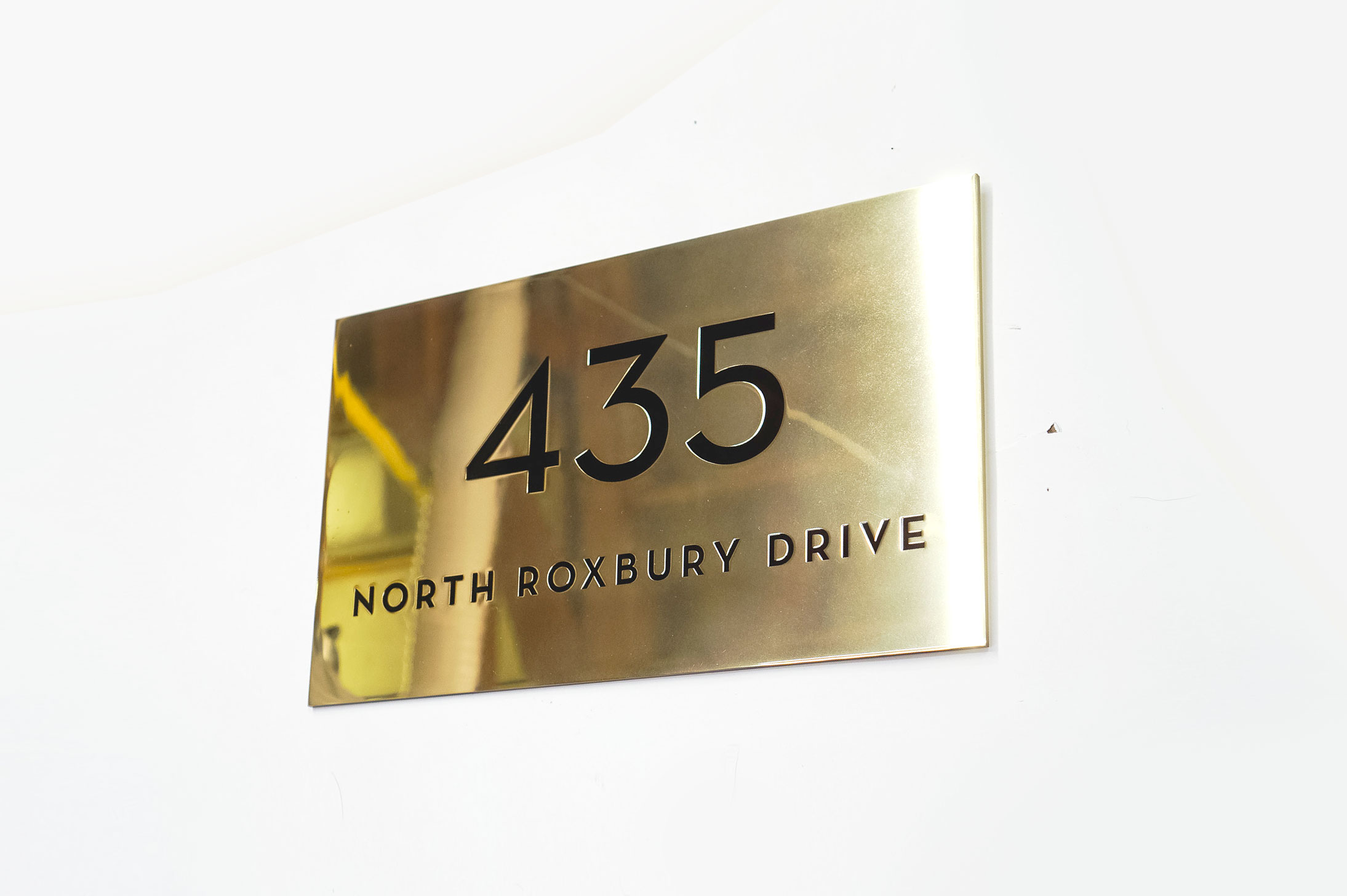 Classic style, solid brass exterior address sign for Mickey's Fine Pharmacy, a Beverly Hills landmark.