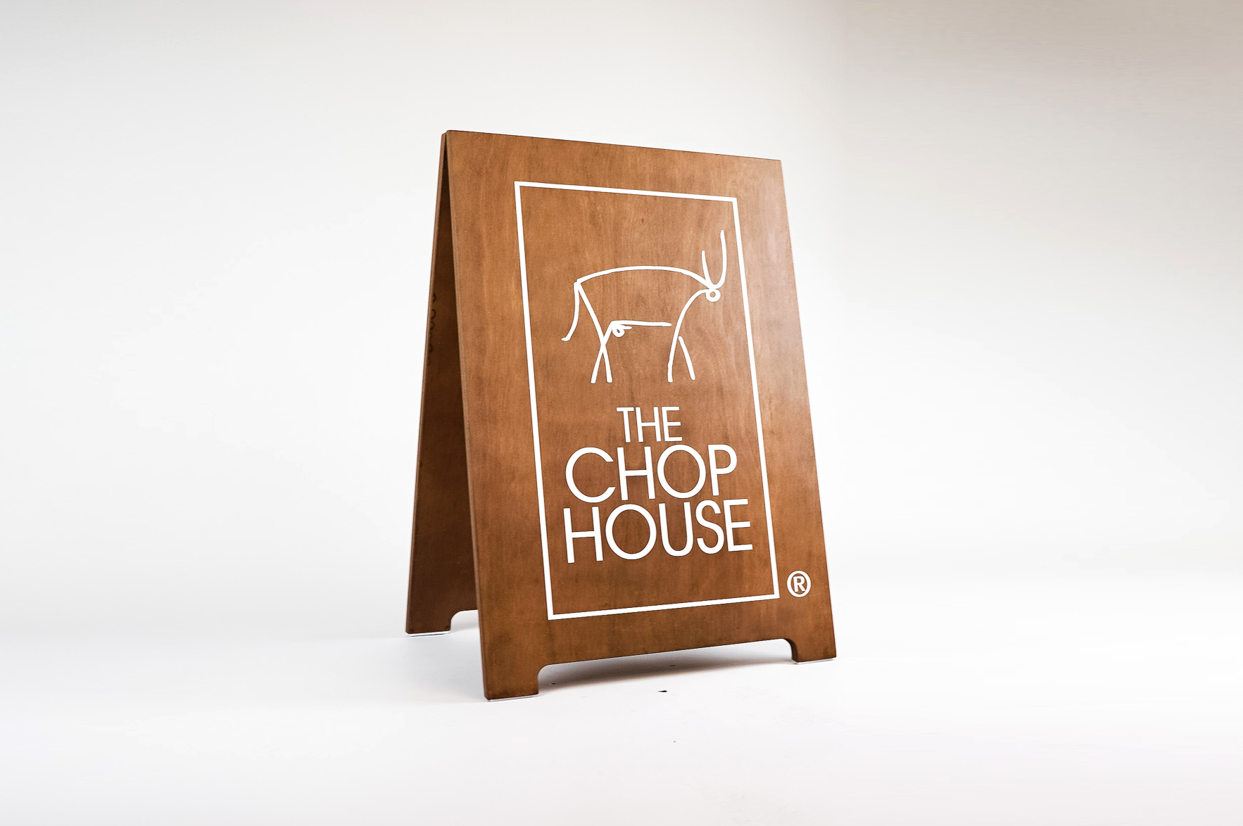 Dark wood sidewalk A-frame sign with white logo for The Chop House, a bar and lounge in Toledo, Ohio.