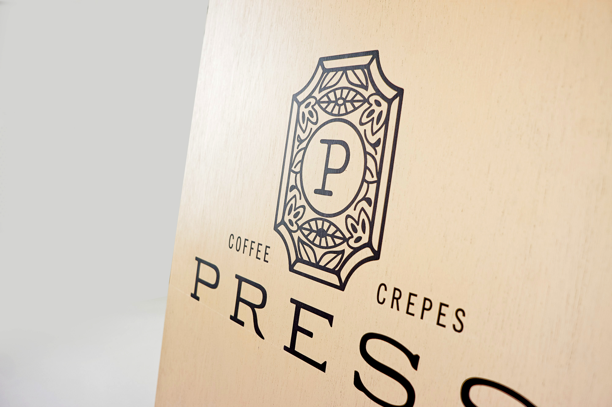 Light wood A-frame sidewalk sign with intricate black logo and text for Press, a European-Inspired coffeehouse and crêperie in downtown Graham, NC.