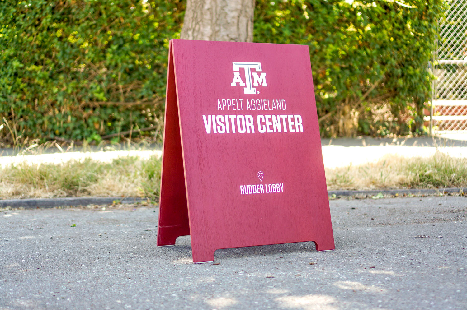 Red A-frame sign with white text for the visitor center at Texas A&M, a public research university in College Station, Texas.