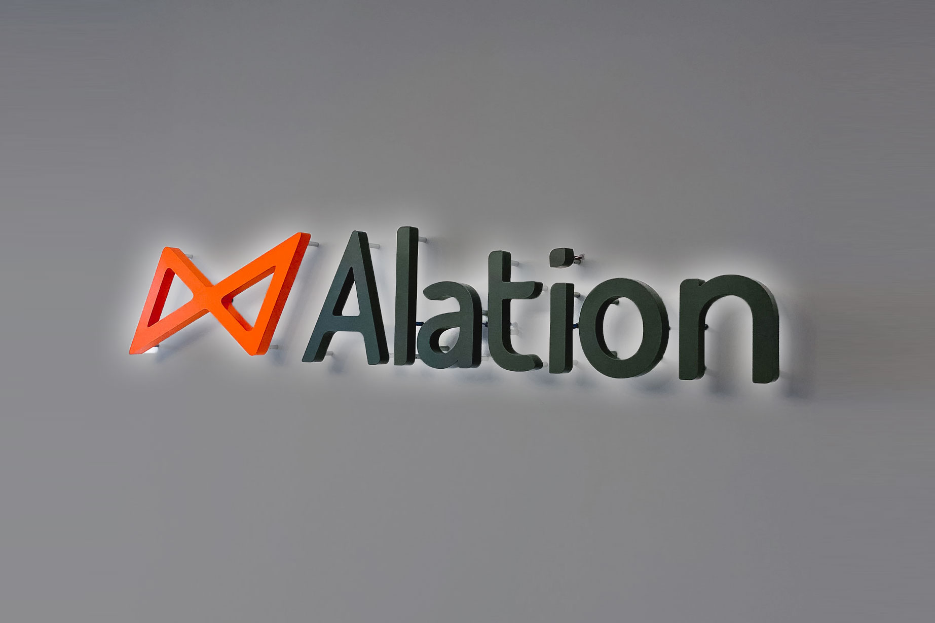 Illuminated black and orange lobby sign on color blocked wall for Alation, a data catalog company based in Redwood City, CA