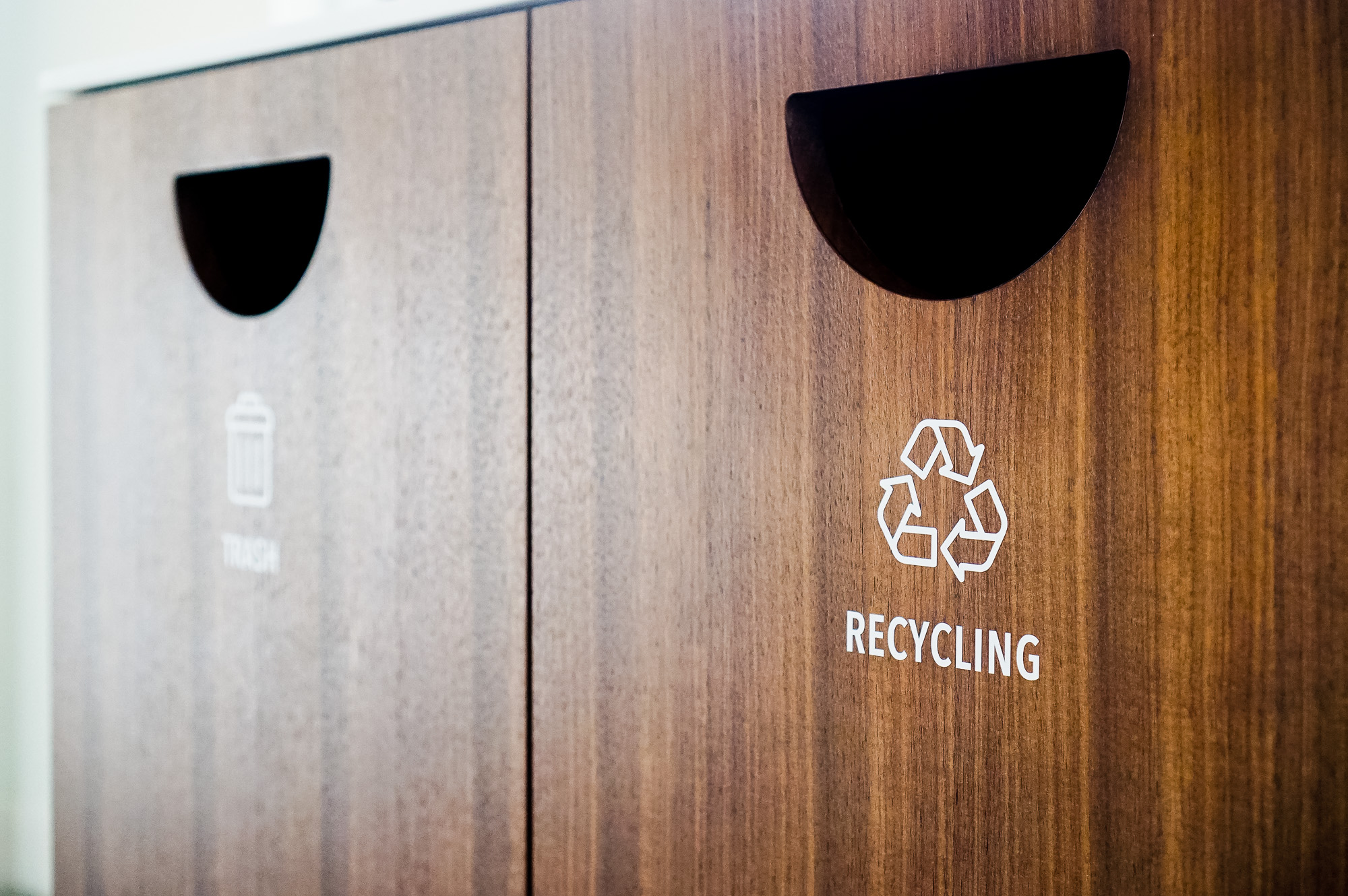 Minimal white vinyl signage /decals for wood trash, compost, and recycling bins at the office of Baker McKenzie, a multinational law firm.