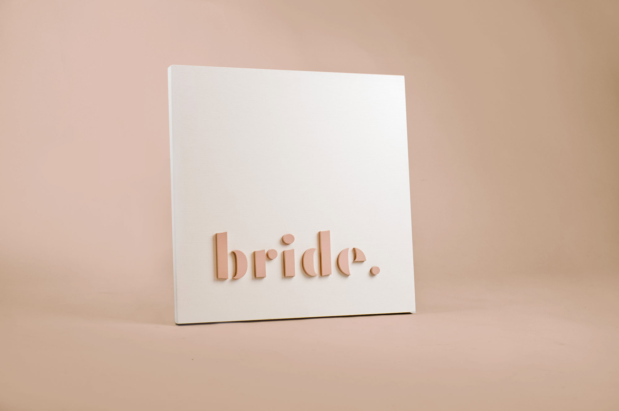 Blush-colored blade sign for Bride, a bridal shop in Kansas City, Missouri.