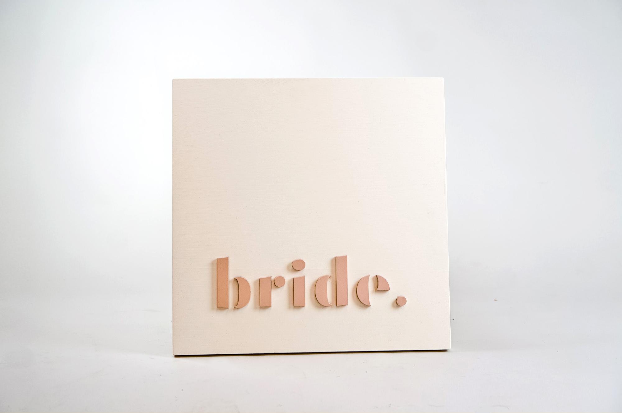 Blush-colored blade sign for Bride, a bridal shop in Kansas City, Missouri.