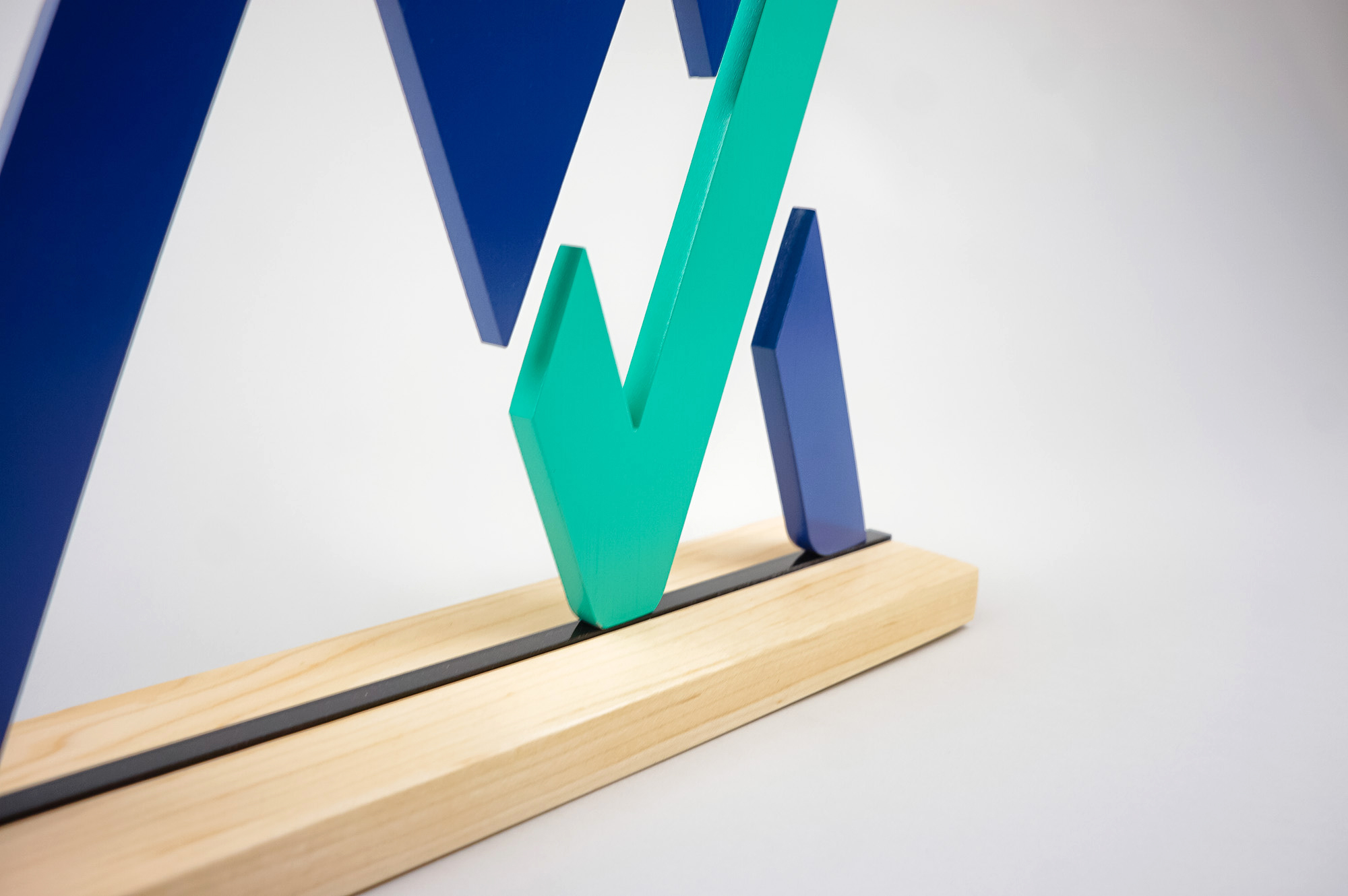 Freestanding blue and green logo on wood base for the office of MyVest, a company building enterprise wealth management technology for the digital age.