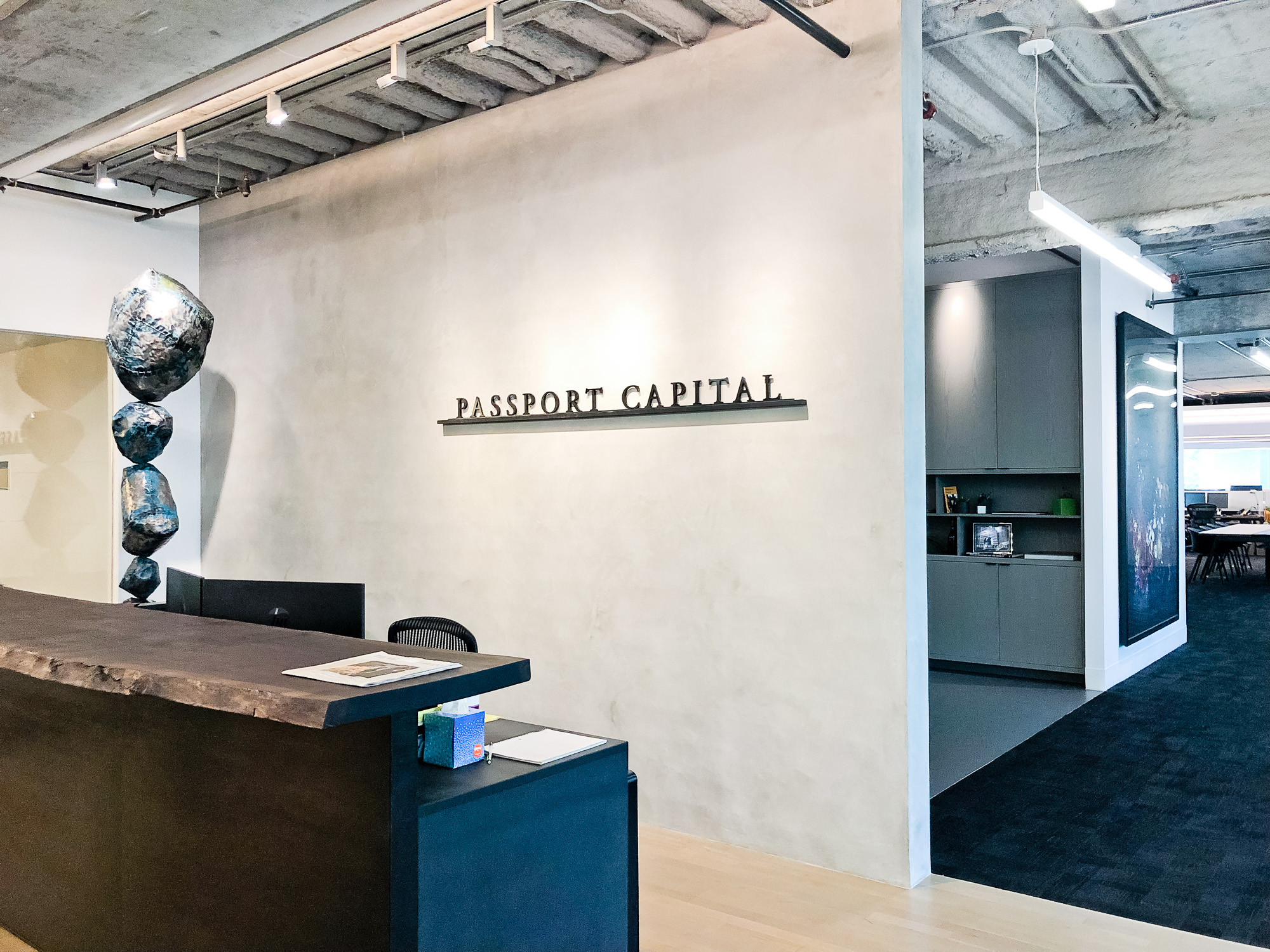 Black letters on shelf against concrete lobby wall at Passport Capital, a San Francisco-based, global thematic investment firm.