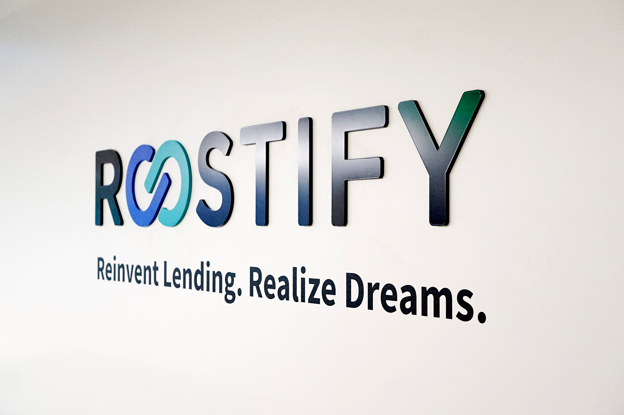 Dimensional, full color logo on white wall in lobby and elevator vestibule for the San Francisco office of Roostify, an integrated digital mortgage software platform.