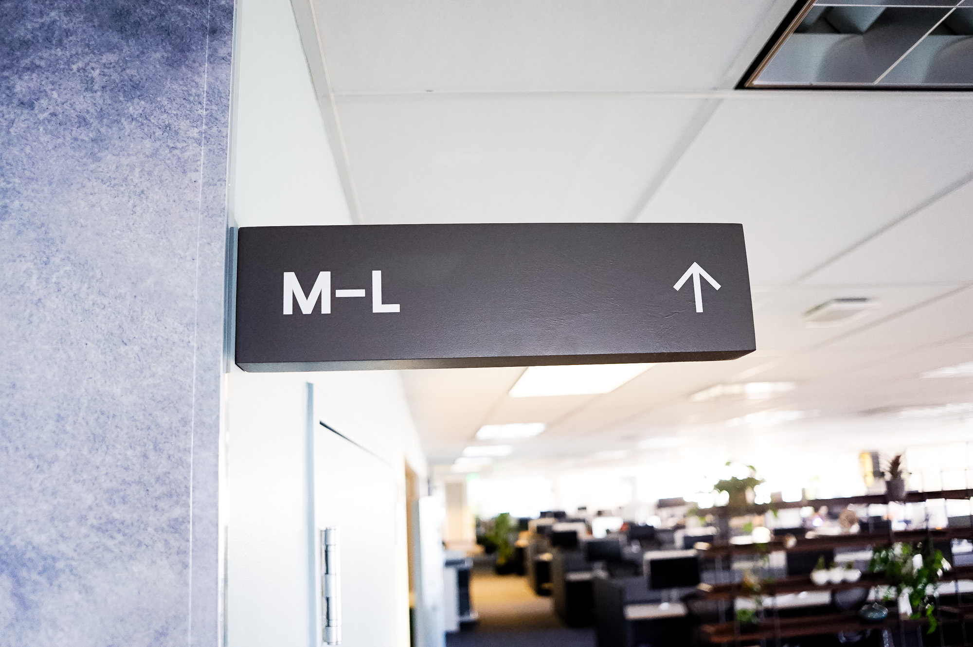 Overhead dark grey wayfinding sign with white text for a San Francisco office of Slack, an American cloud-based set of proprietary team collaboration tools and services.