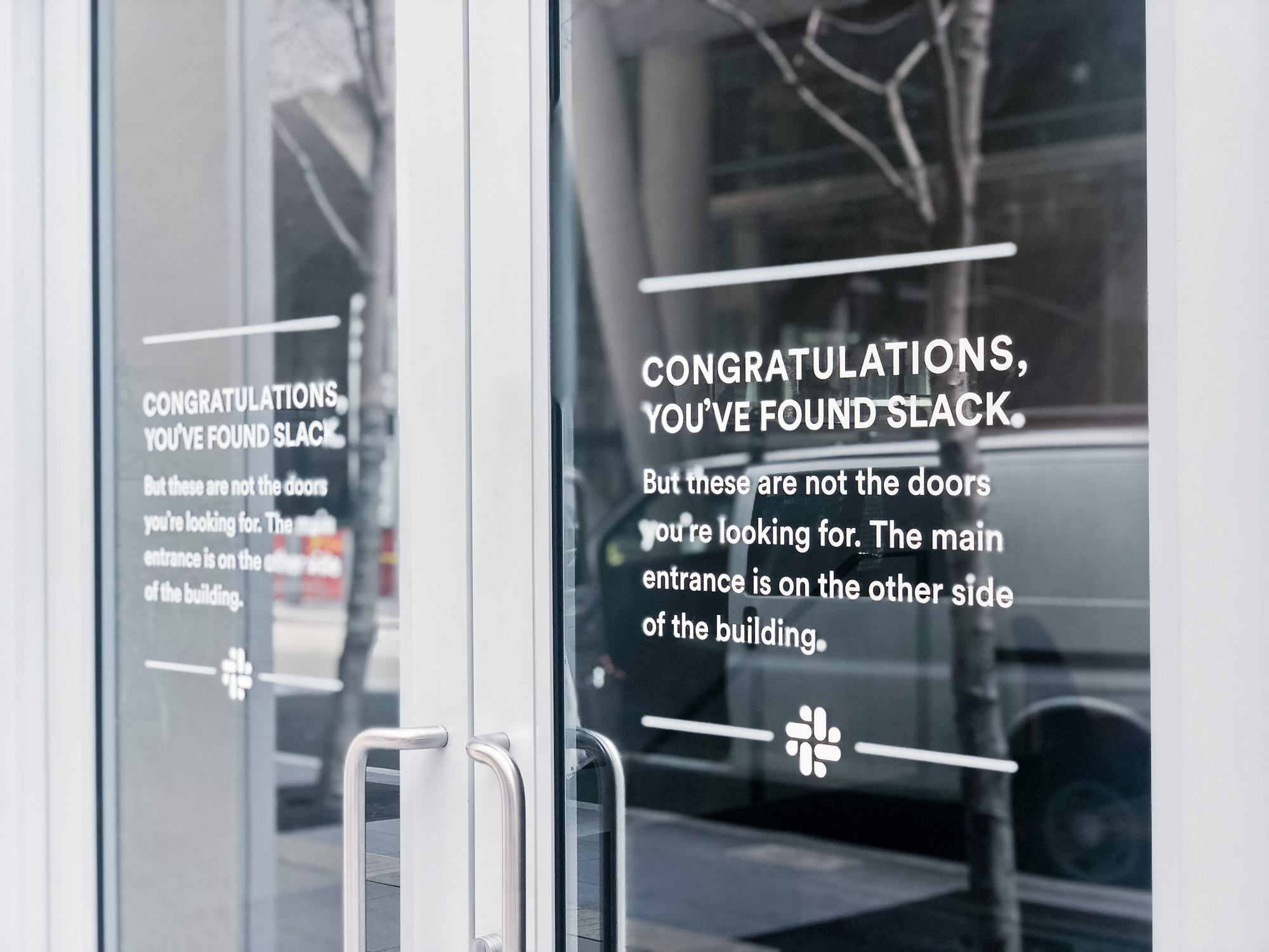 Matte white vinyl wayfinding sign with white text on glass doors for the San Francisco office of Slack, an American cloud-based set of proprietary team collaboration tools and services.