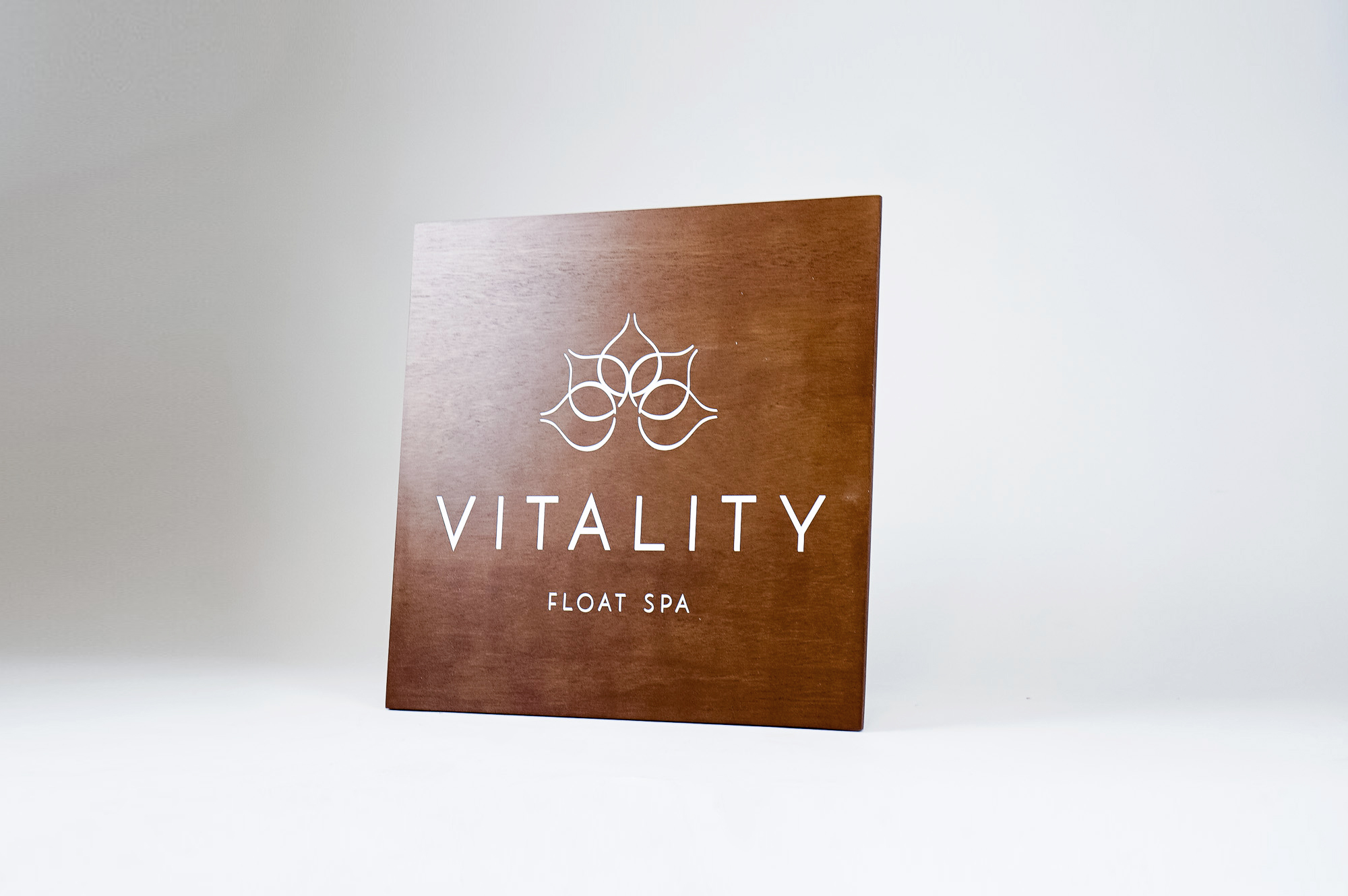 Dark wood retail blade sign with white artwork for Vitality, a massage therapy and wellness studio located in Carytown, Virginia.
