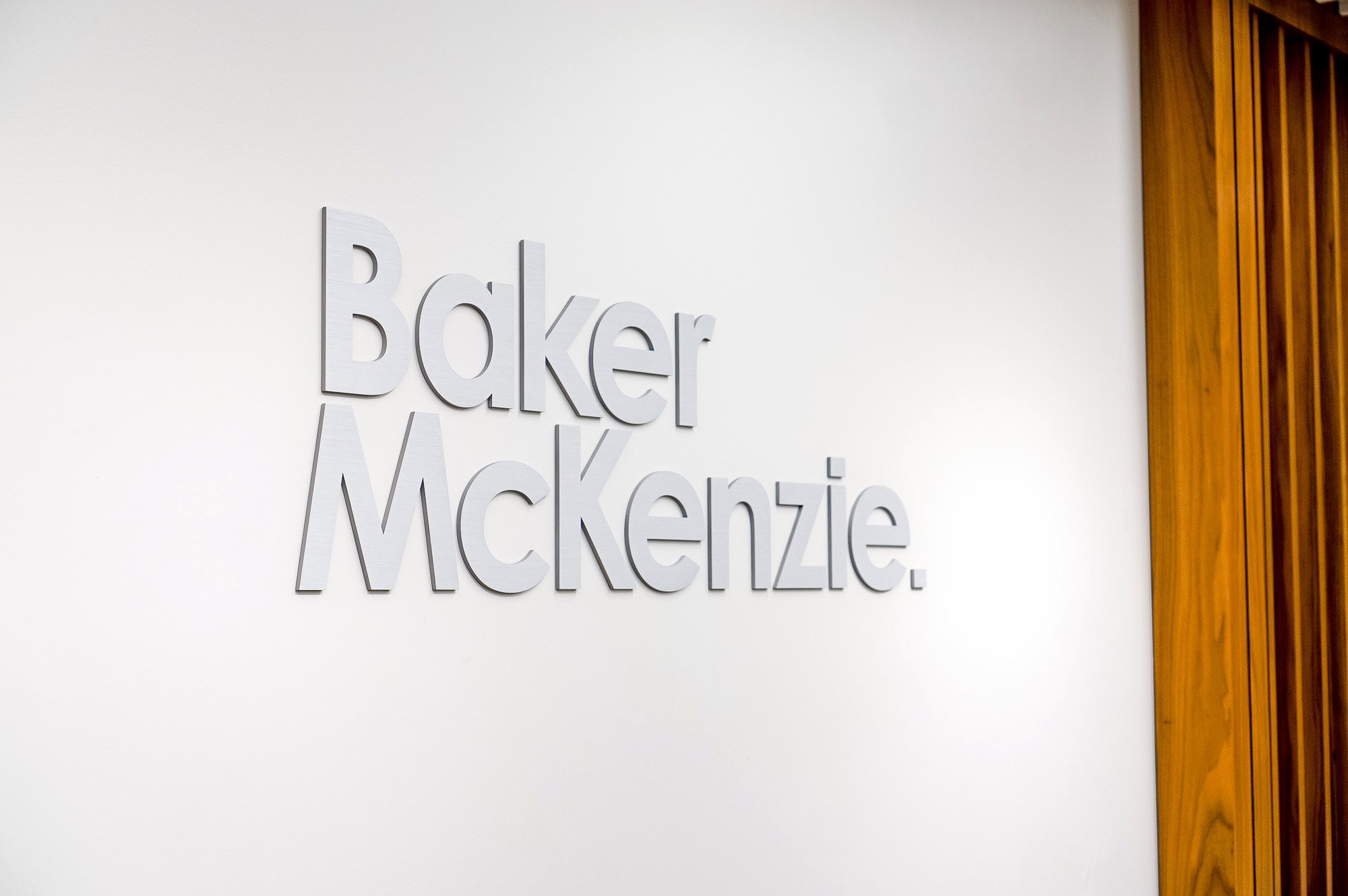 Brushed metal lobby sign on white wall at the office of Baker McKenzie, a multinational law firm.