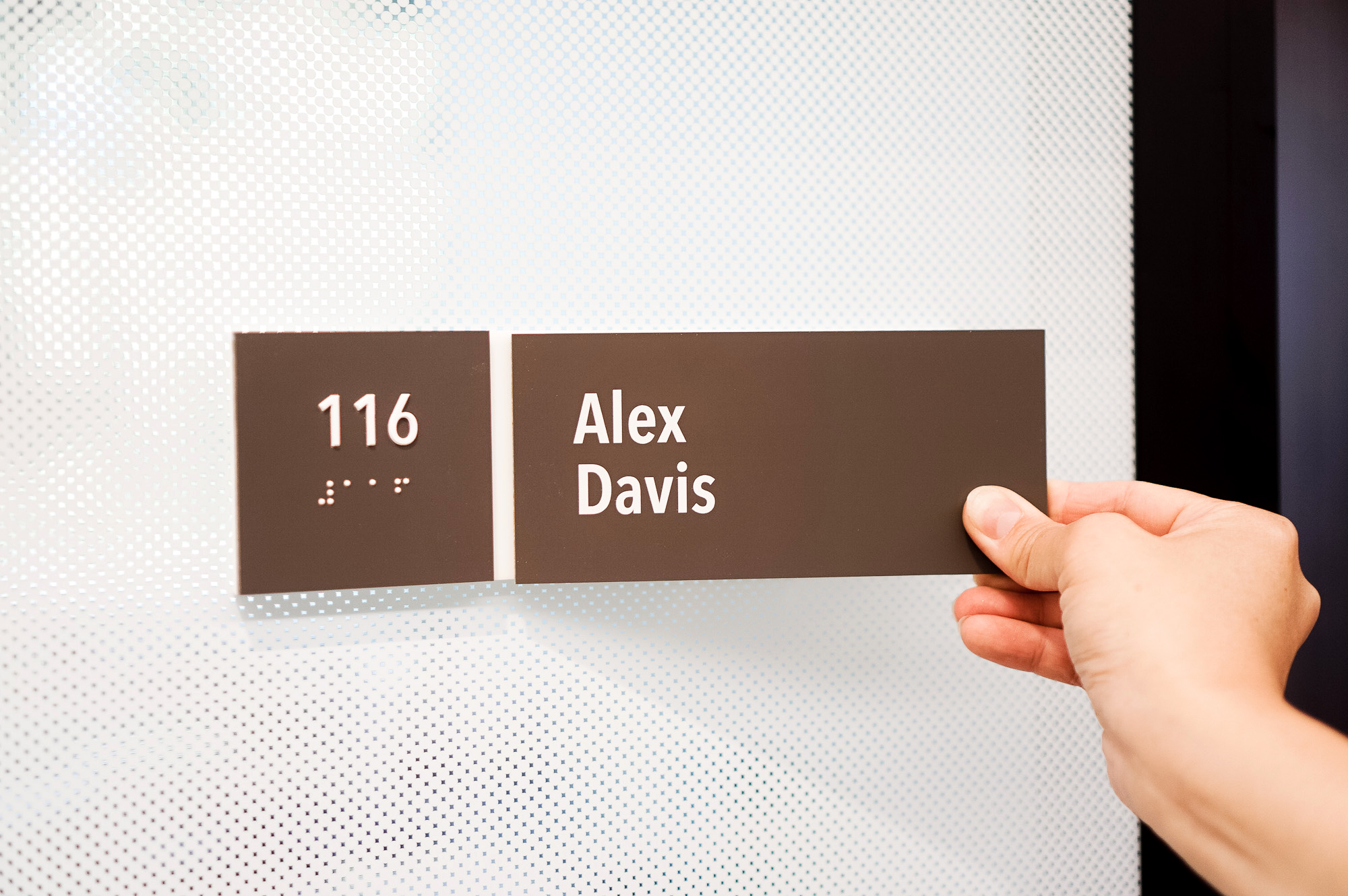 Changeable, minimal grey office ADA nameplate signs for Baker McKenzie, a multinational law firm.
