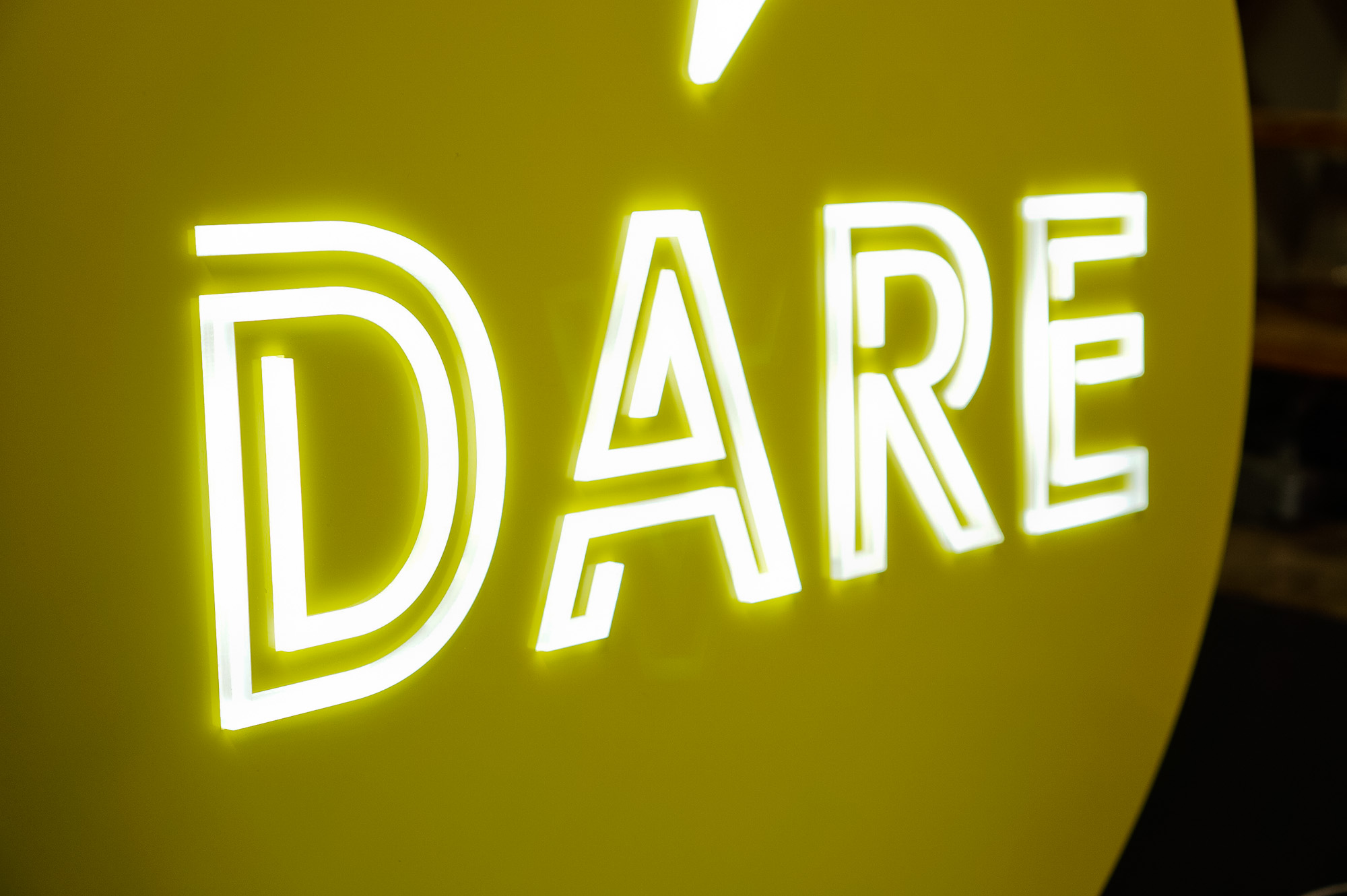 Yellow neon-style team sign for Facebook, an American online social media and social networking service company.