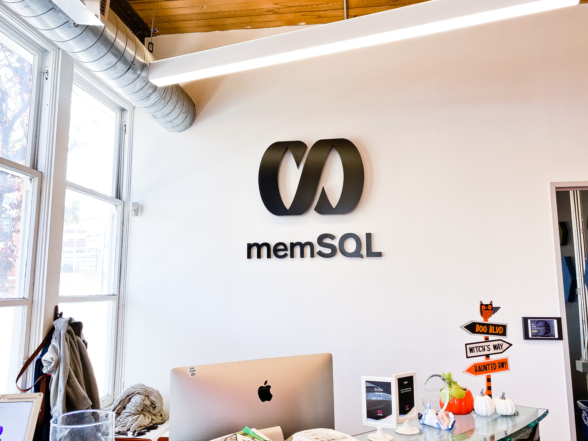 Illuminated black sign with back-lit purple lights for memSQL, a software company in San Francisco, California.