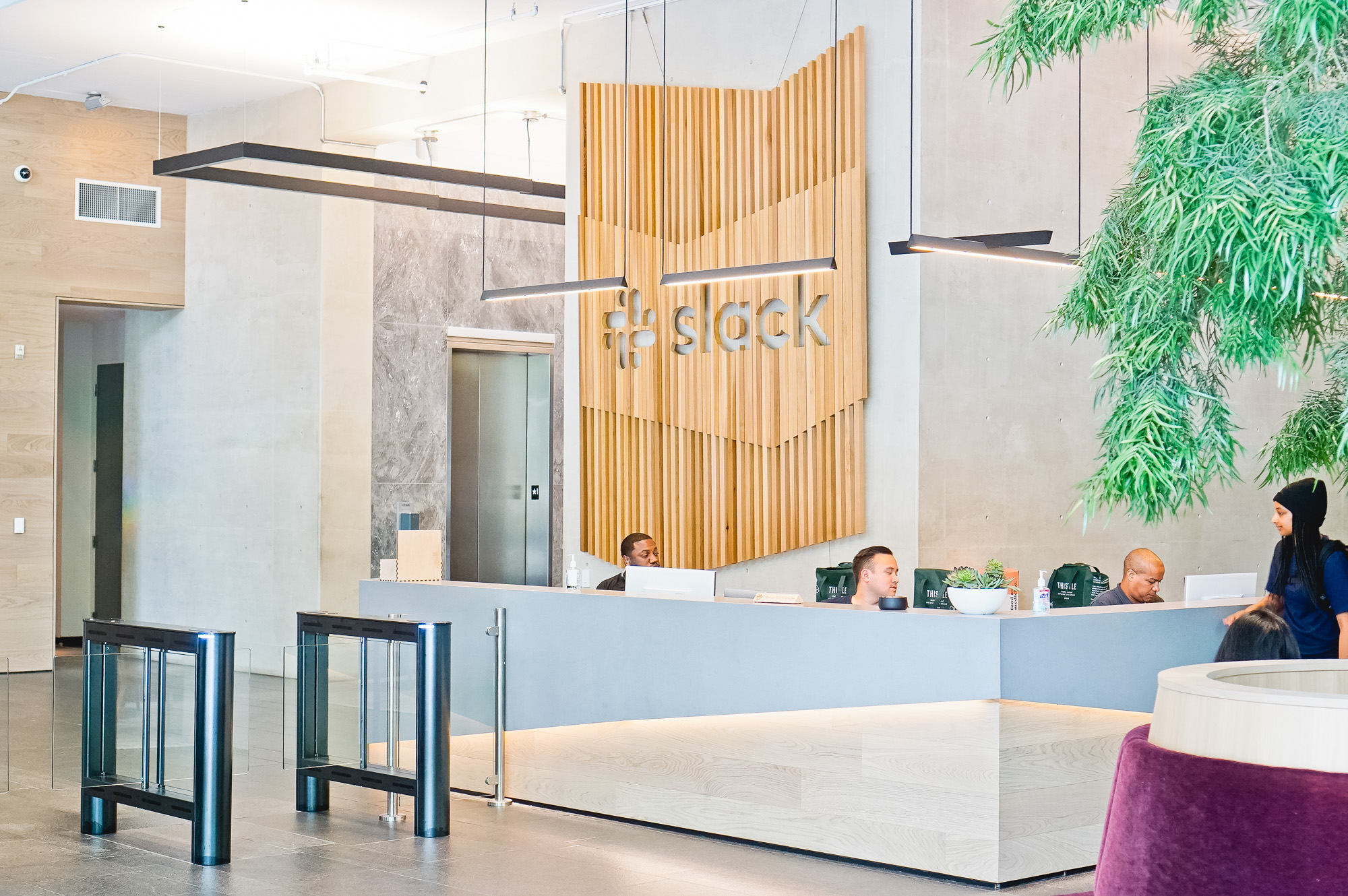 Modern, large-scale slat wood lobby sign on concrete wall at the San Francisco lobby of Slack, an American cloud-based set of team collaboration tools and services.