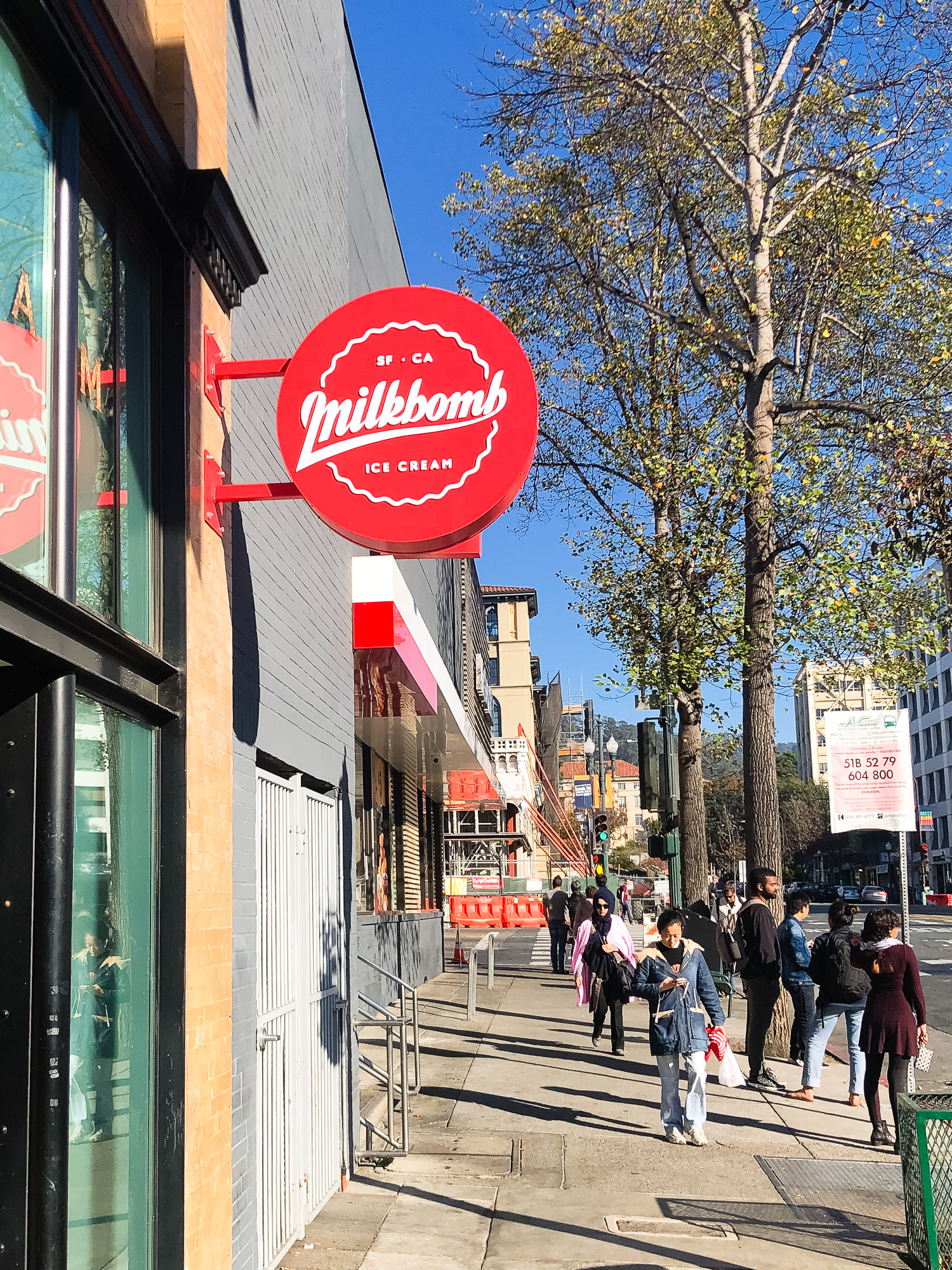 Red circular blade sign with white script for Milkbomb, a sweet stop for donut ice cream sandwiches.