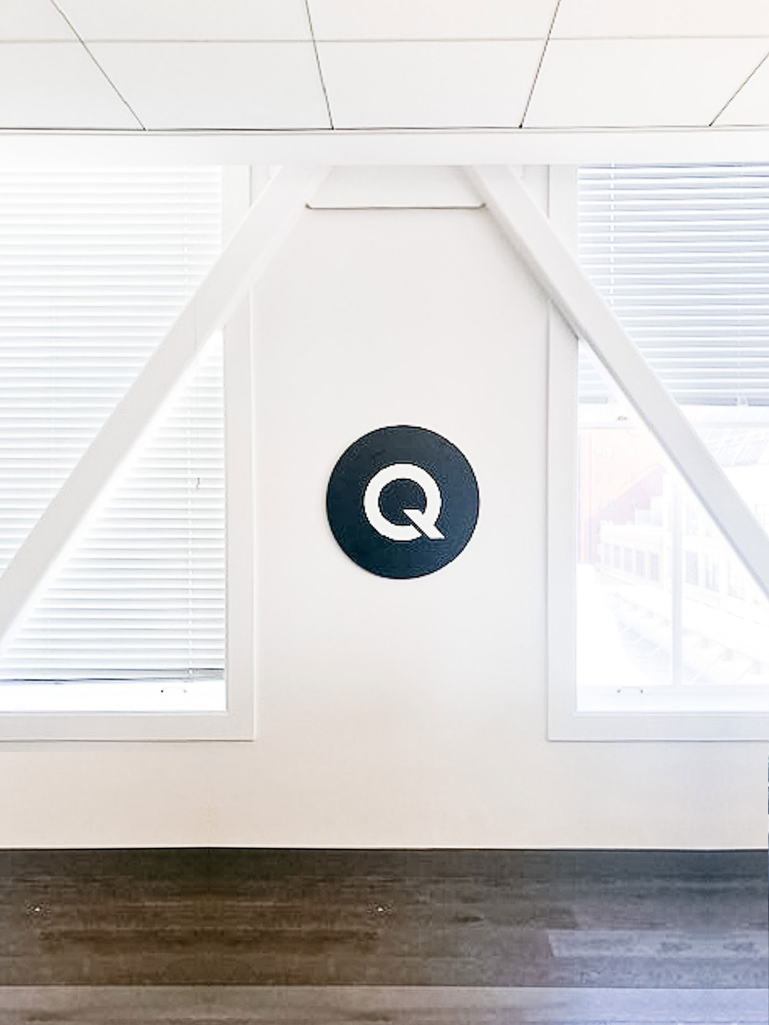 Black and white circular sign on white wall for the office of Qordoba, a content AI technology to help organizations achieve consistency and clarity across all types of content.