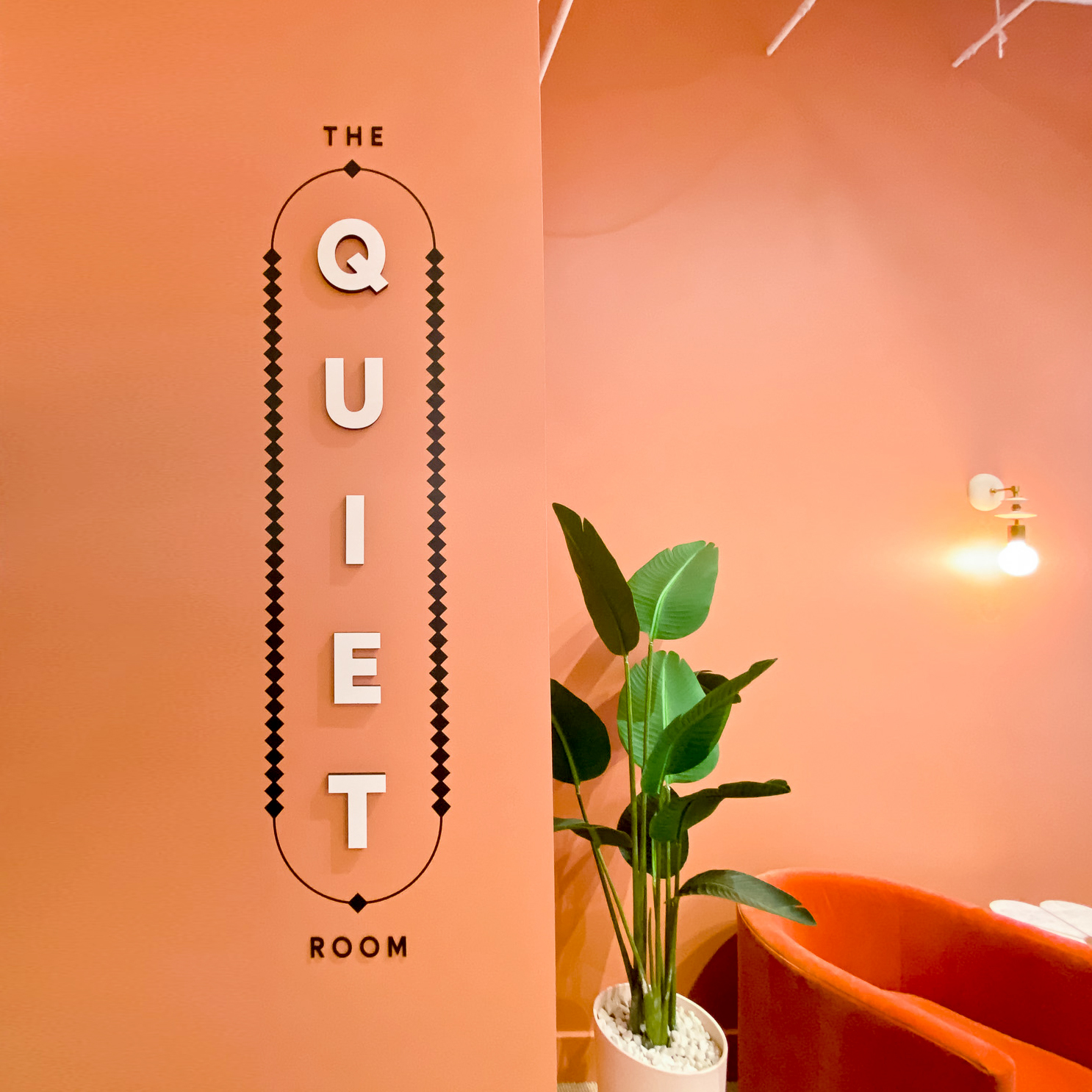 "Multi-dimensional black and white ""The Quiet Room"" sign on salmon colored wall for the San Francisco expansion of The Wing, a network of work and community spaces designed for women."