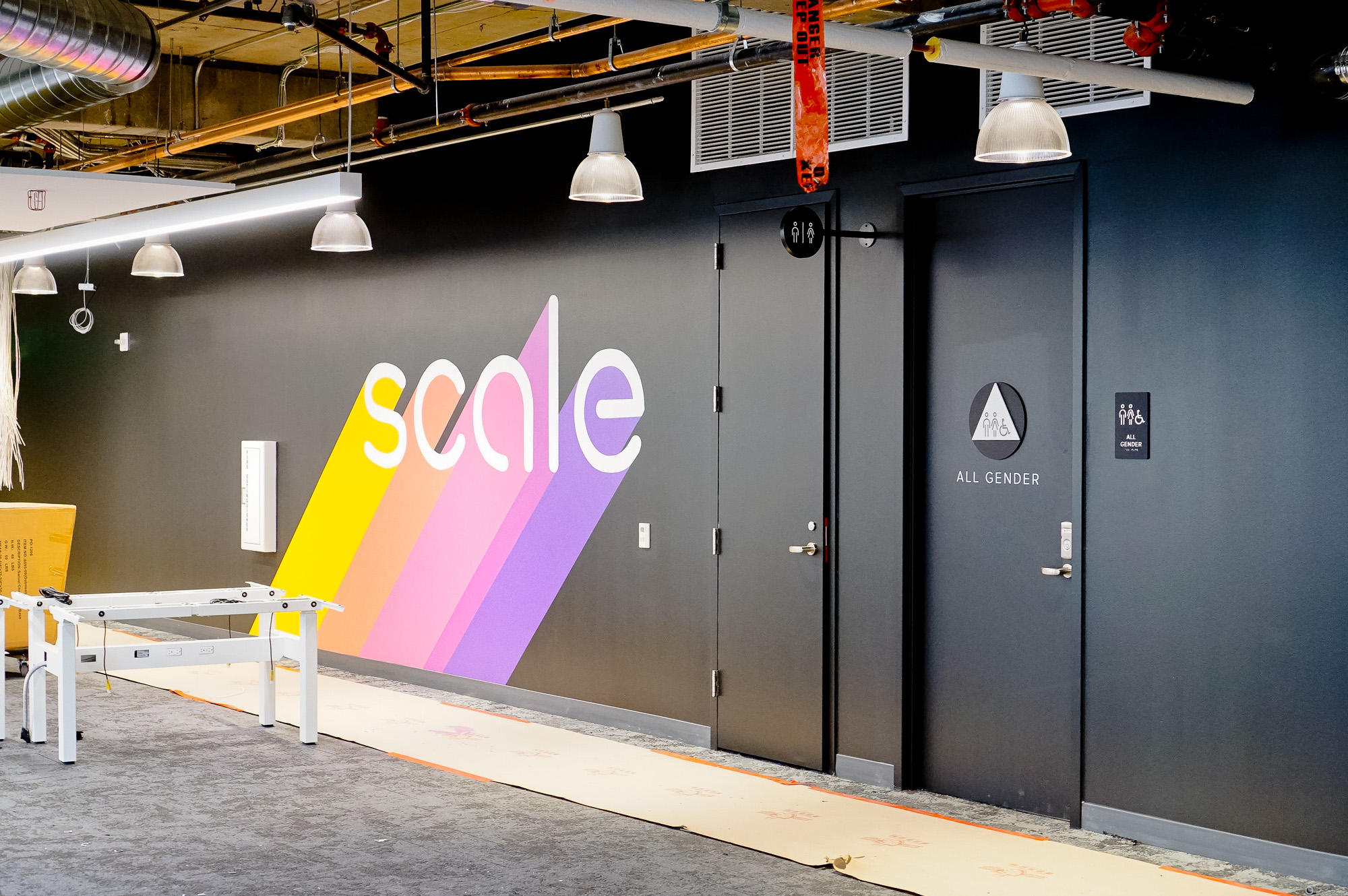 Modern, matte black restroom signs with white icons on black walls for the restrooms of Scale, a San Francisco based company delivering high quality training data for AI applications such as self-driving cars, mapping, AR/VR, robotics, and more.
