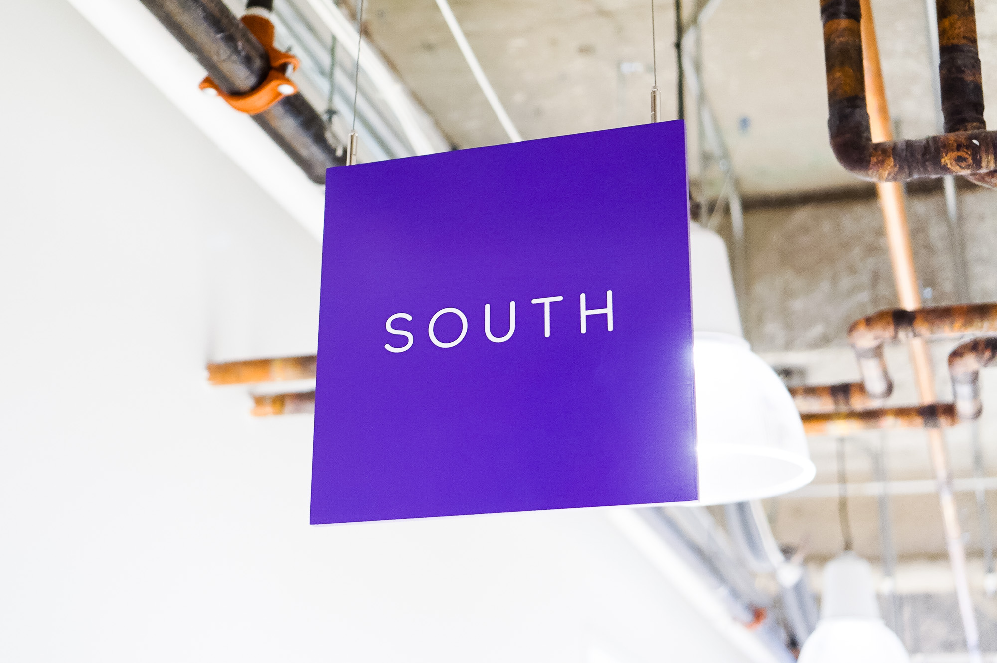 Minimal, multi-colored north, south, east, and west suspended directional signs for Scale, a San Francisco based company delivering high quality training data for AI applications such as self-driving cars, mapping, AR/VR, robotics, and more.