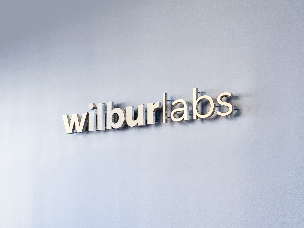 Illuminated, back-lit metal sign on slate colored wall for Wilbur Labs, a San Francisco-based startup studio building a portfolio of companies.