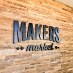 Black distressed wood sign on reclaimed wood wall at the checkout stand / register area for the Napa, CA location of Makers Market, a handcrafted marketplace where you can shop the best of American made goods.