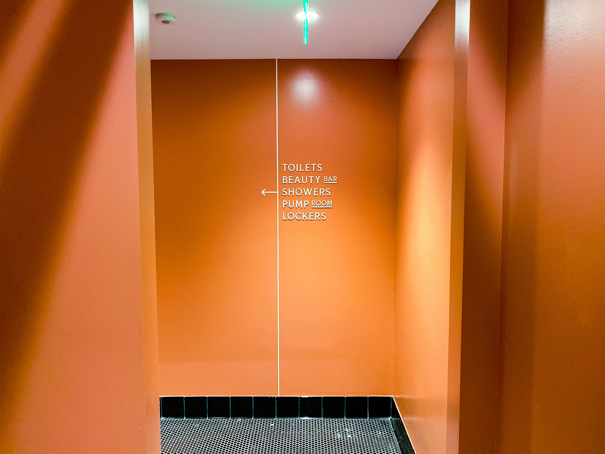 Cream colored, typographic wayfinding sign on orange wall for The Wing, a co-working space in San Francisco.
