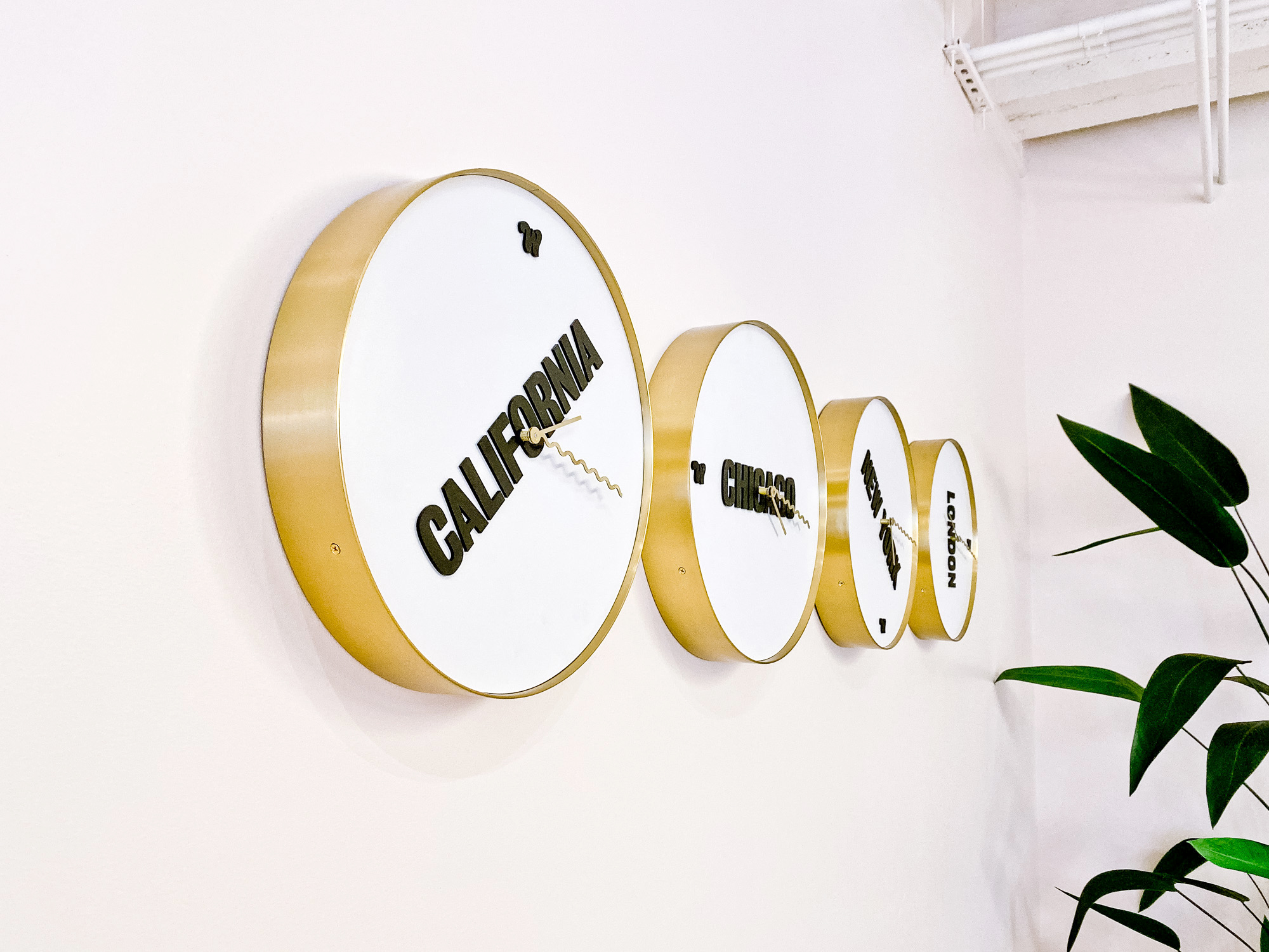 Custom brass and white international time zone clock wall for the San Francisco expansion of The Wing, a network of work and community spaces designed for women.