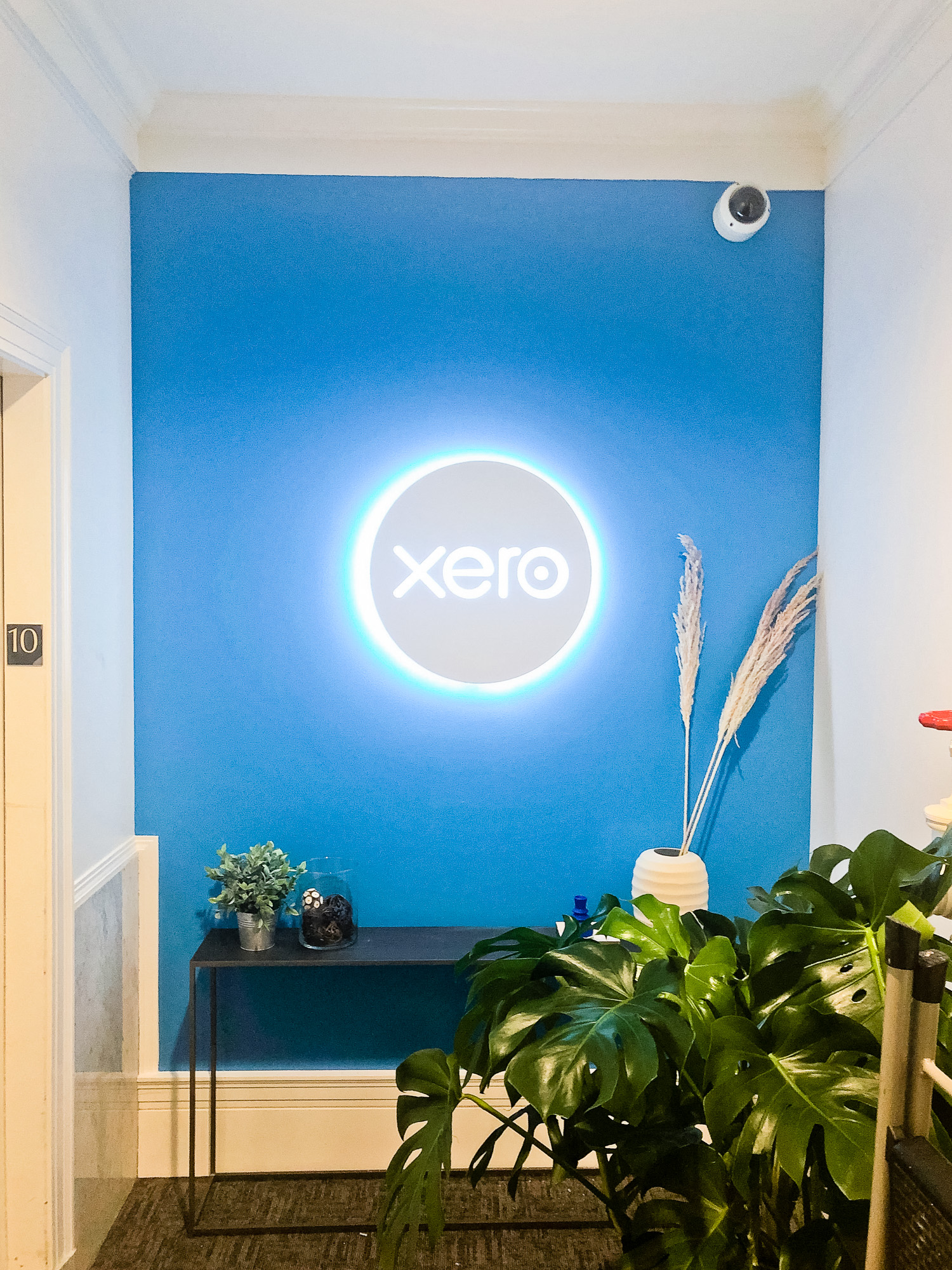 Illuminated, back-lit white sign on blue lobby wall for Xero, a cloud-based accounting software platform for small and medium-sized businesses.