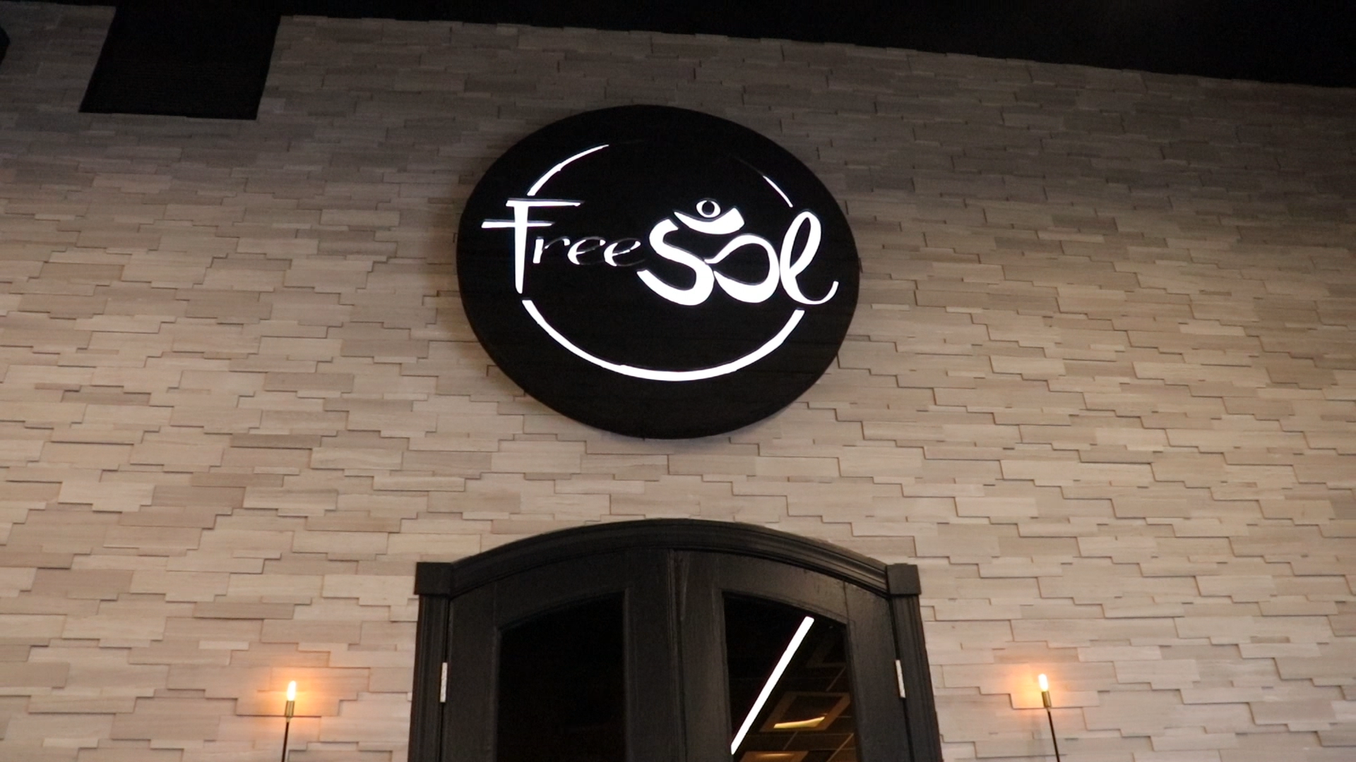 Torched wood, interior-lit, large circular wall sign for FreeSol, a fitness studio located in Styles Studios, a boutique fitness studio in Peoria, IL.