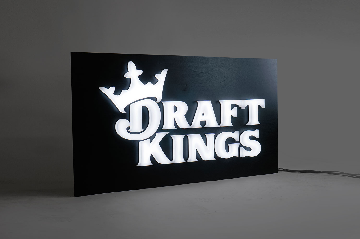 Illuminated, face-lit white logo on a black painted backer/wall for the San Francisco office of Draft Kings, an American daily fantasy sports contest and sports betting provider.